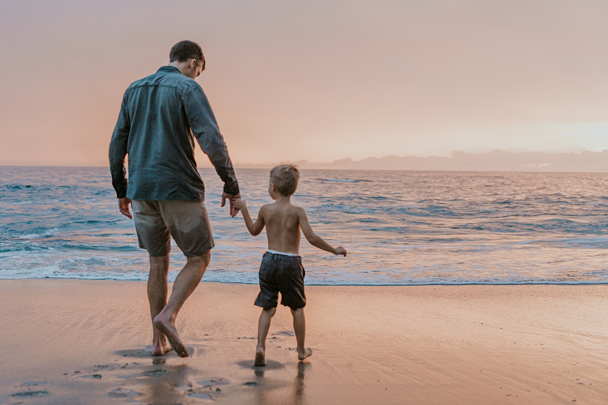 Orange County family photographer. Photo of dad and his son walking off into the red sunset at Table Rock Beach Laguna Beach during outdoor family photo session