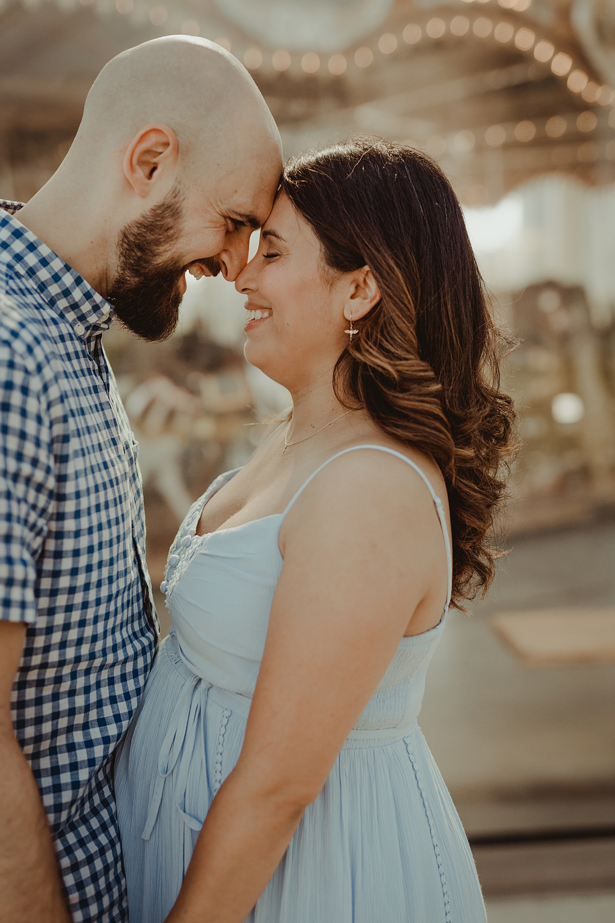 Orange County family photographer. Photo of expecting mom and dad standing in front of a carousel during outdoor maternity photo session with Krystil McDowall Photography
