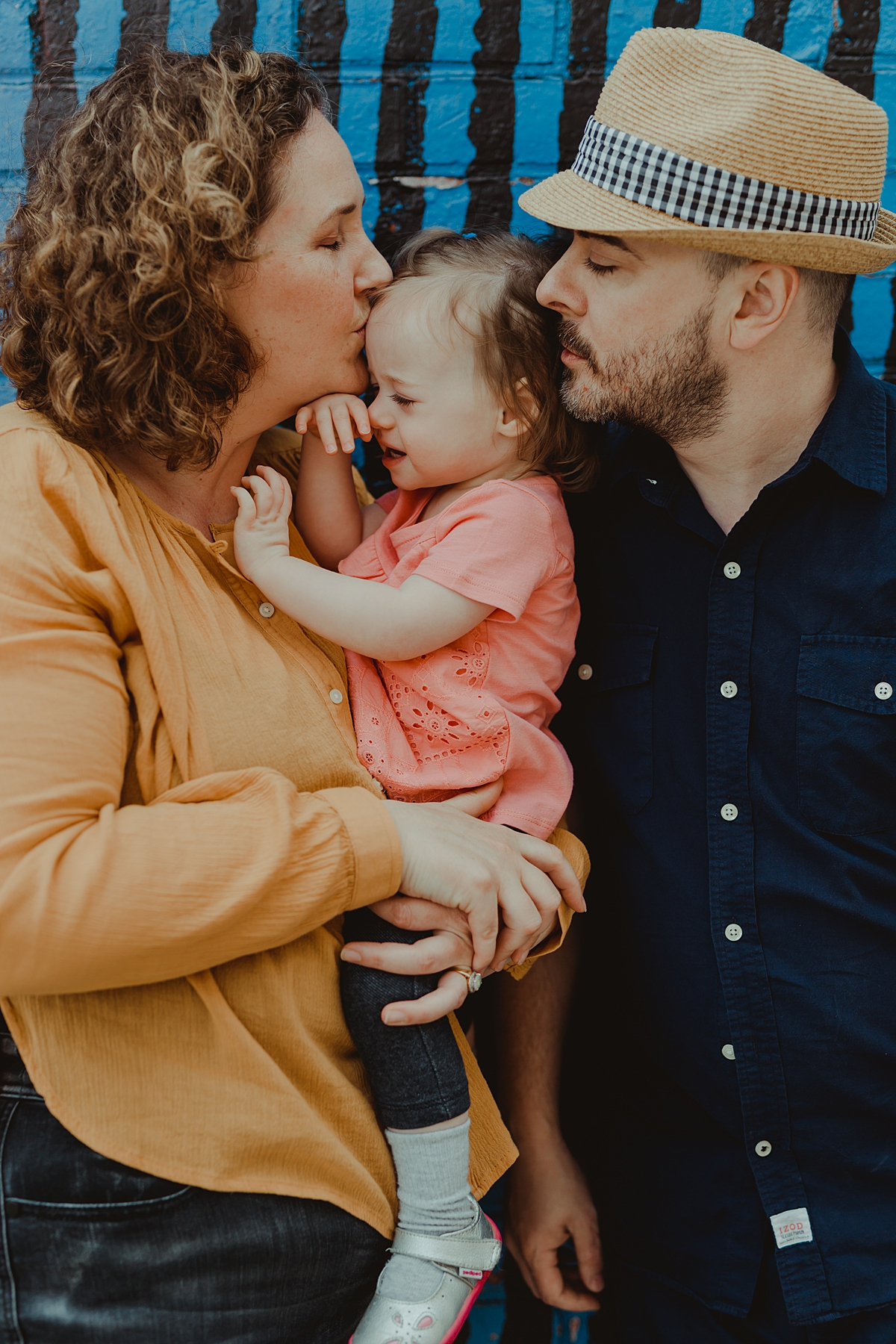 Orange County family photographer. Photo of mom and dad kissing their young two year old daughter during outdoor family photo session with Krystil McDowall Photography