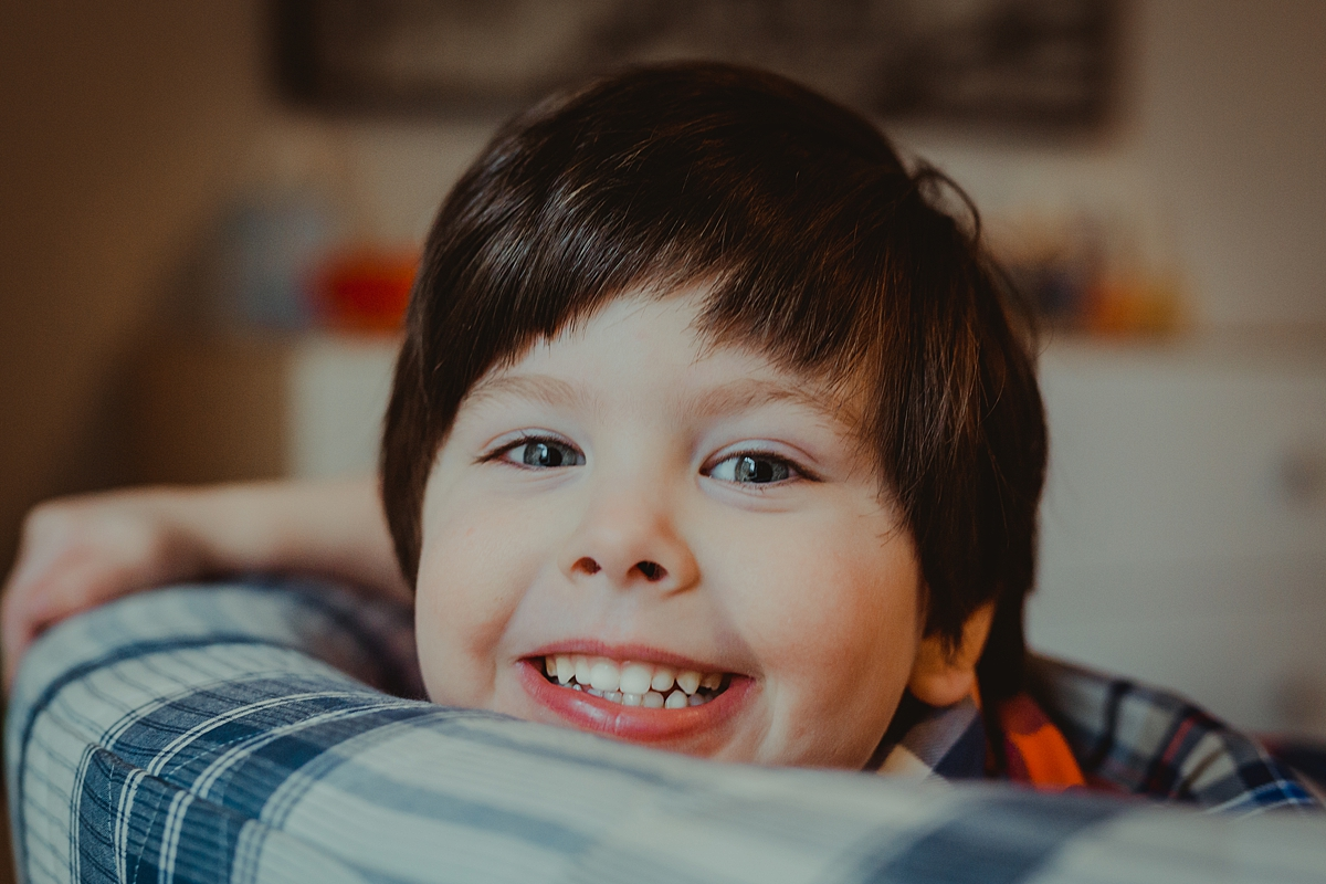 Orange County family photographer. Portrait of young boy as he peeks over the chair in his color bedroom during in home family photo session with Krystil McDowall Photography