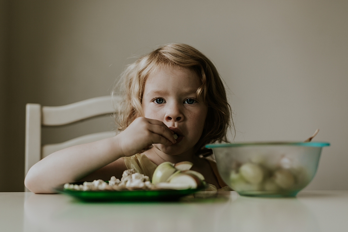 Orange County family photographer. Photo of young red haired girl having a snack of apples at her kitchen table during family photo shoot in Huntington Beach Orange County