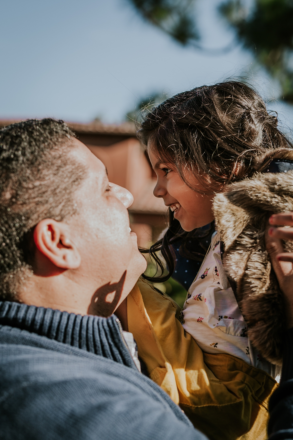 Orange County family photographer. Dad pl;aying with his sweet black haired daughter in the sunshine during family photo shoot at abandoned railway tracks in orange county