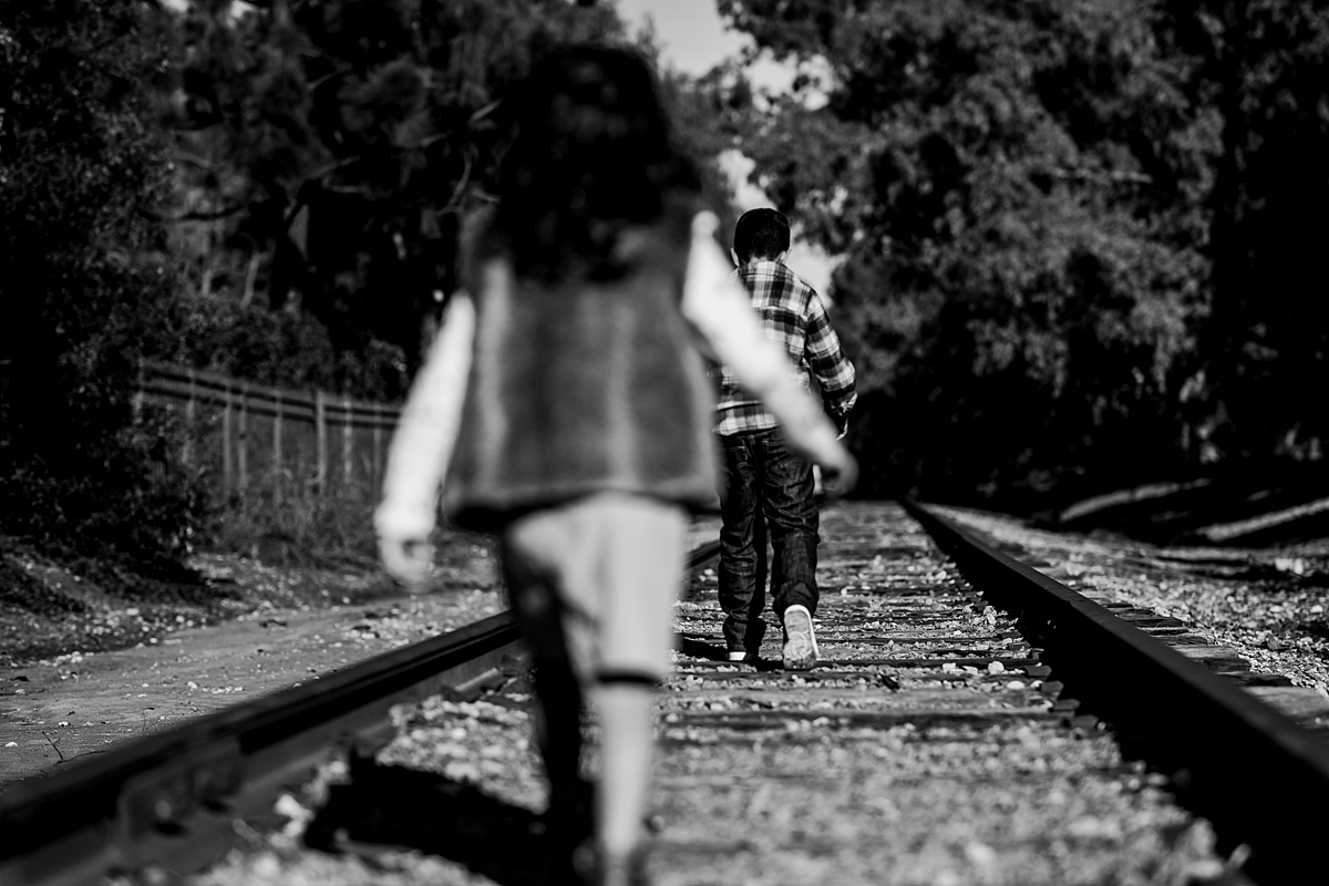 Orange County family photographer. Brother and sister walk along abandoned railway tracks during family photo shoot in orange county