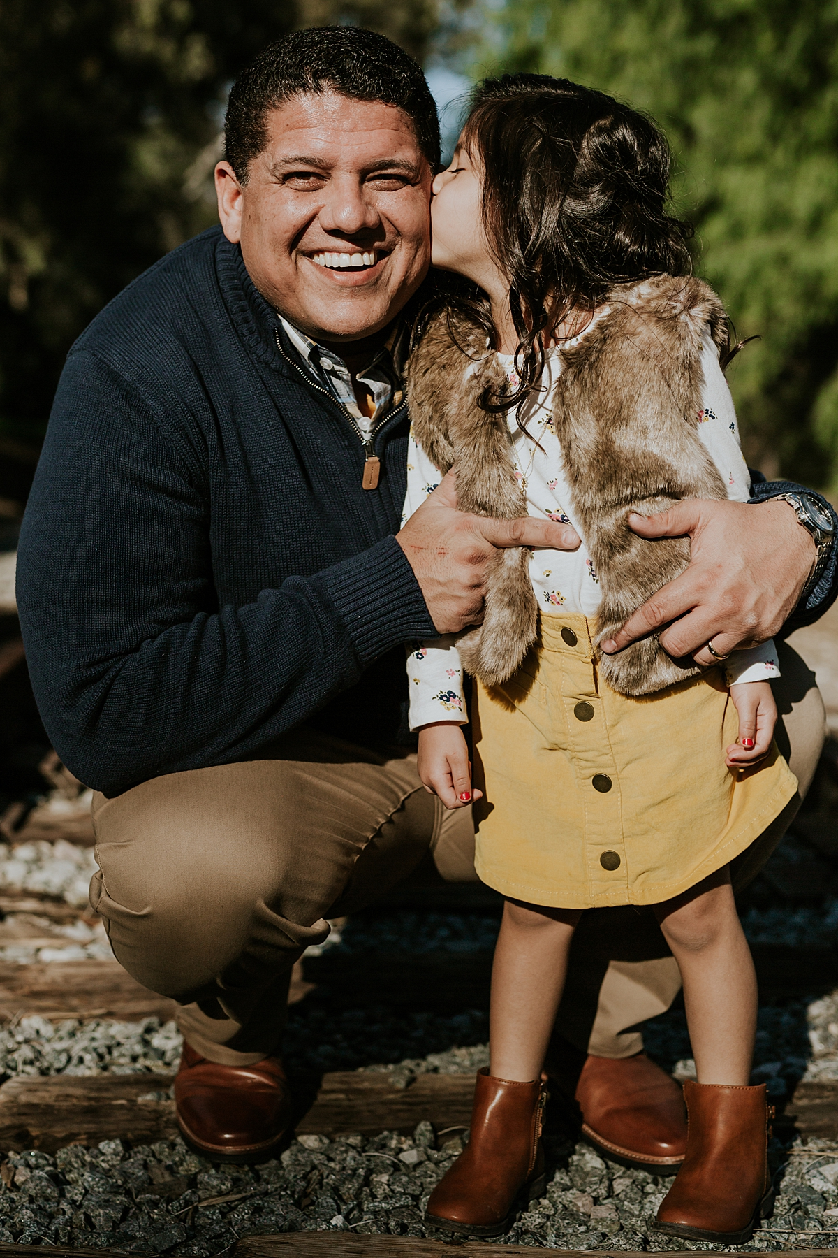 Orange County family photographer. Dad gets a kiss from his sweet black haired daughter while standing on abandoned railroad tracks during family photo shoot in orange county