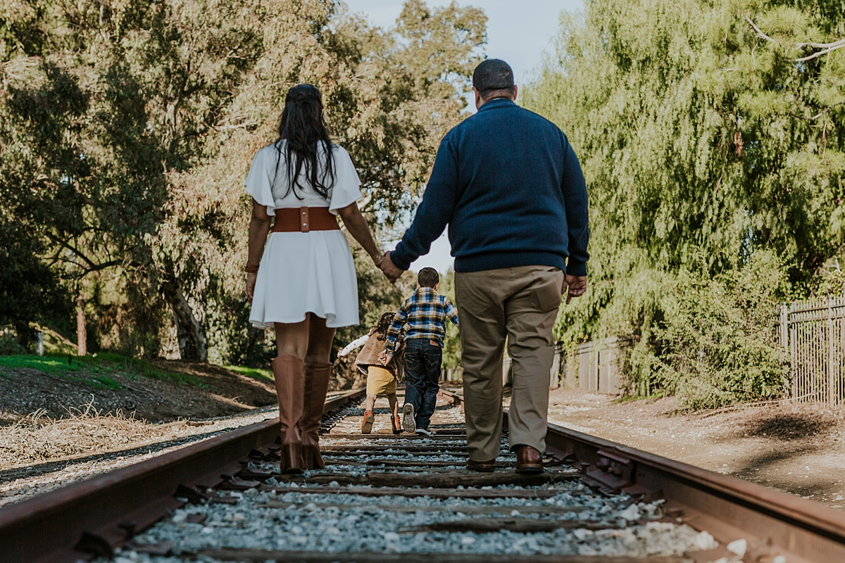 Orange County family photographer. Photo of brother and sister playing on abandoned railway tracks shot through mom and dad holding hands during outdoor family photo shoot in orange county california