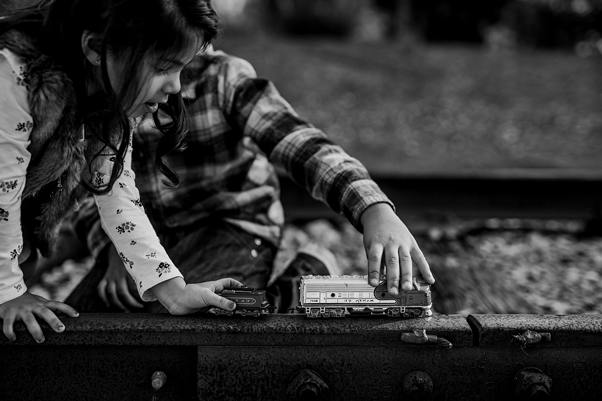 Orange County family photographer. Black and white photo of brother and sister playing with toy trains on abandoned railway tracks during outdoor family photo shoot in orange county california