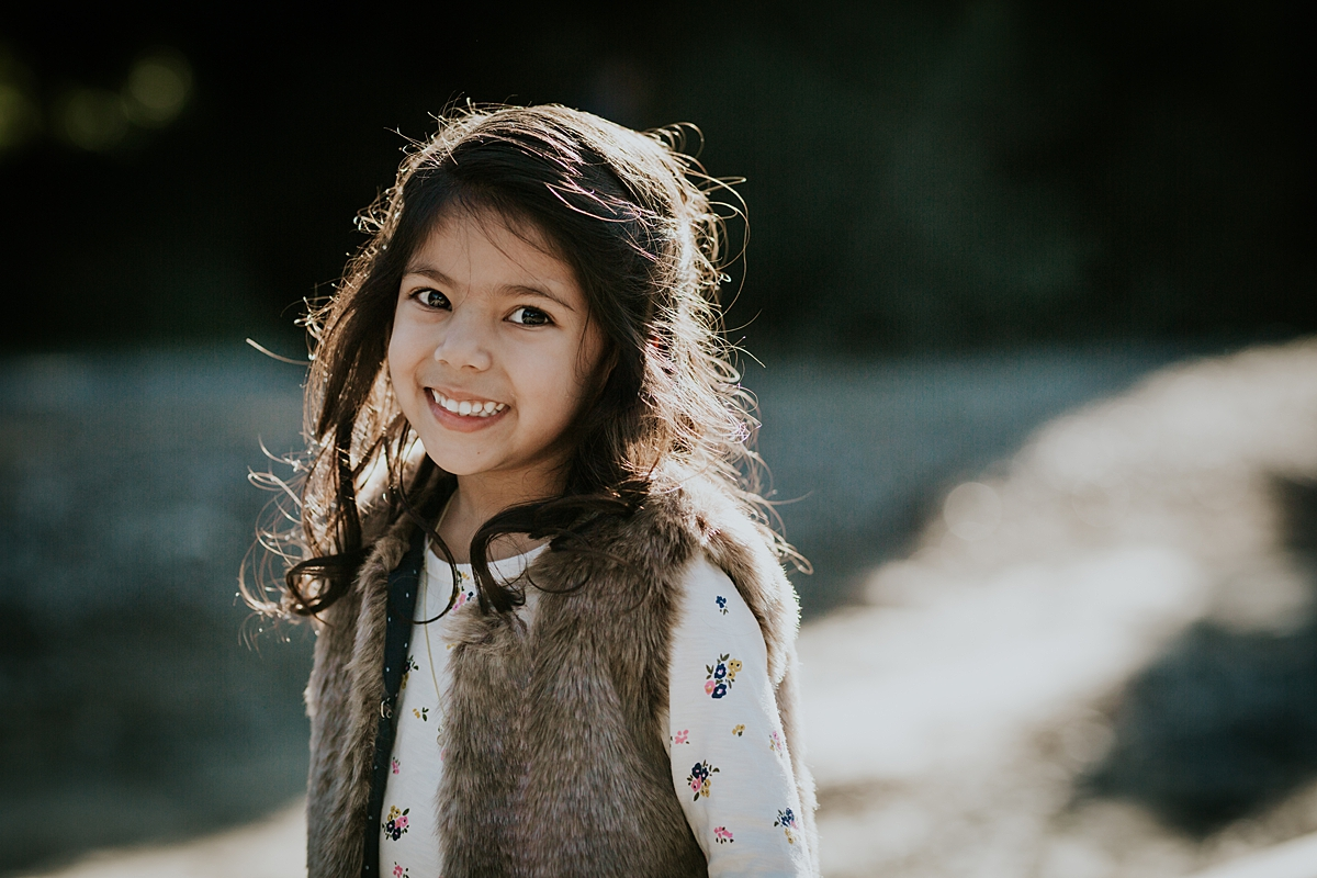 Orange County family photographer. Backlit portrait of young girl at abandoned railway tracks taken during outdoor family photo shoot in orange county
