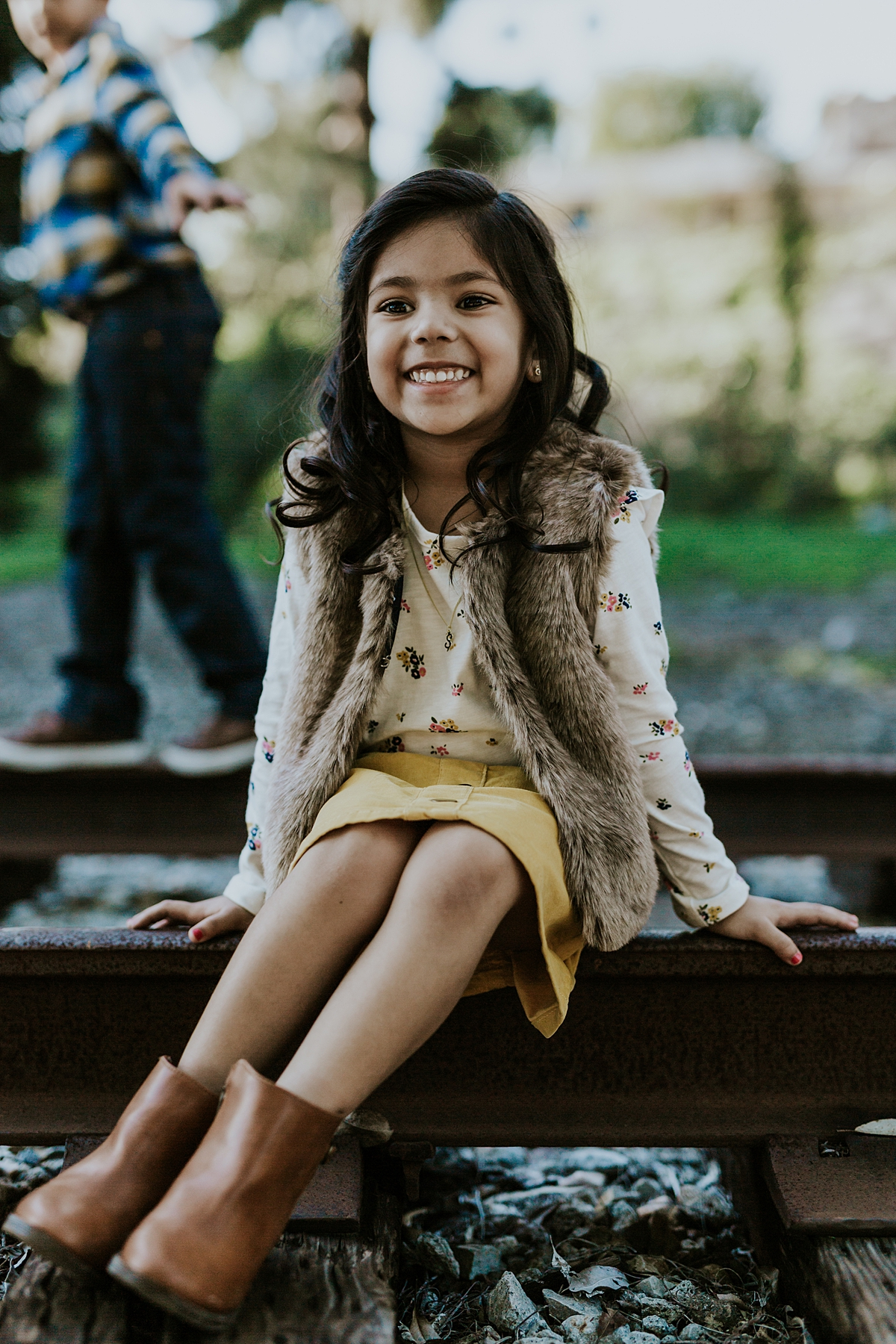 Orange County family photographer. Portrait of young girl in mustard skirt sitting on abandoned railway tracks with brother in the background during outdoor family photo shoot in orange county