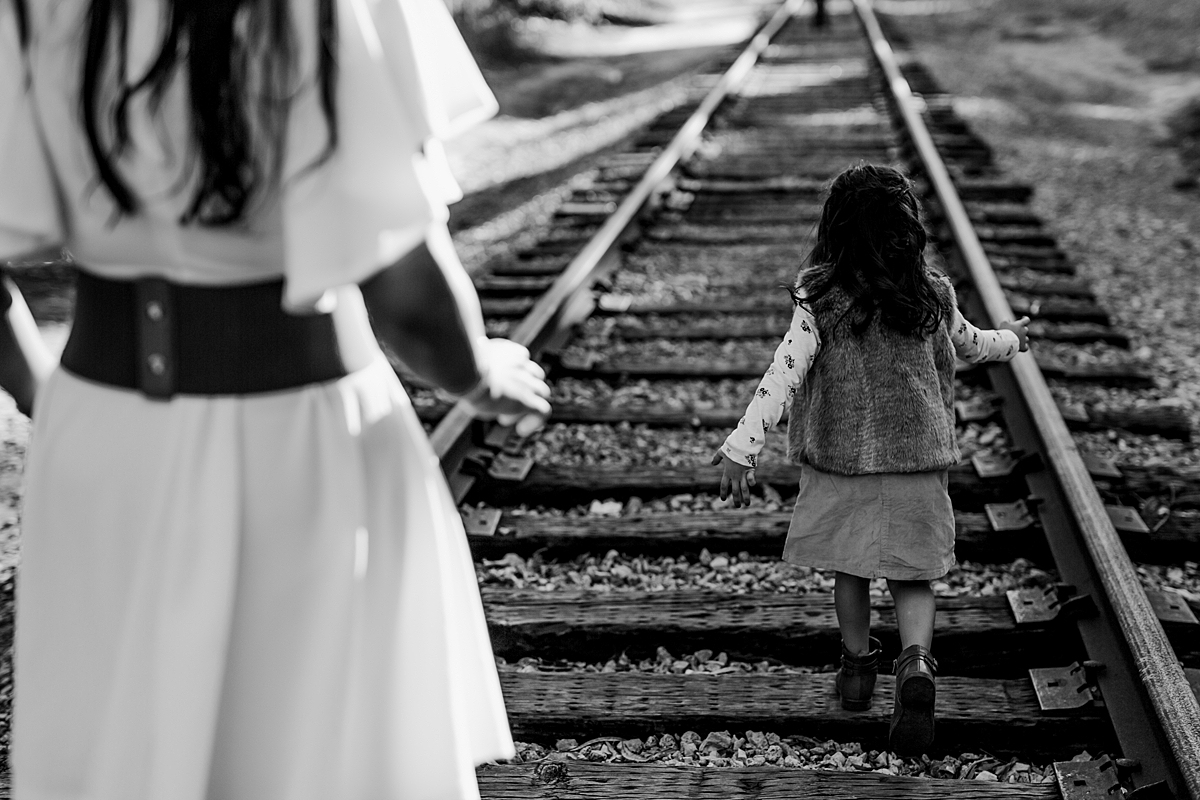 Orange County family photographer. Candid photo of mom looking at daughter as she walks along abandoned railway tracks during outdoor family photo shoot in orange county