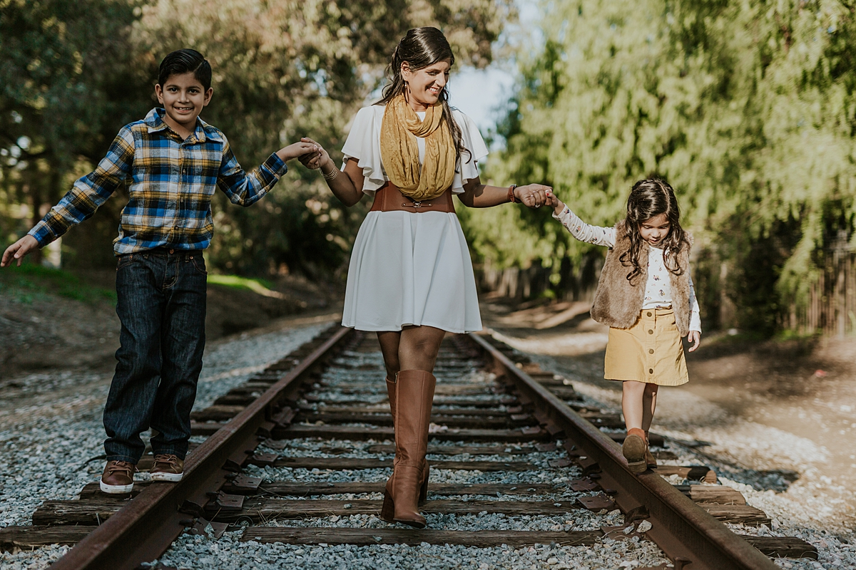 Orange County family photographer. Candid photo of mom holding son and daughter's hands as they walk along abandoned railway tracks during outdoor family photo shoot in orange county