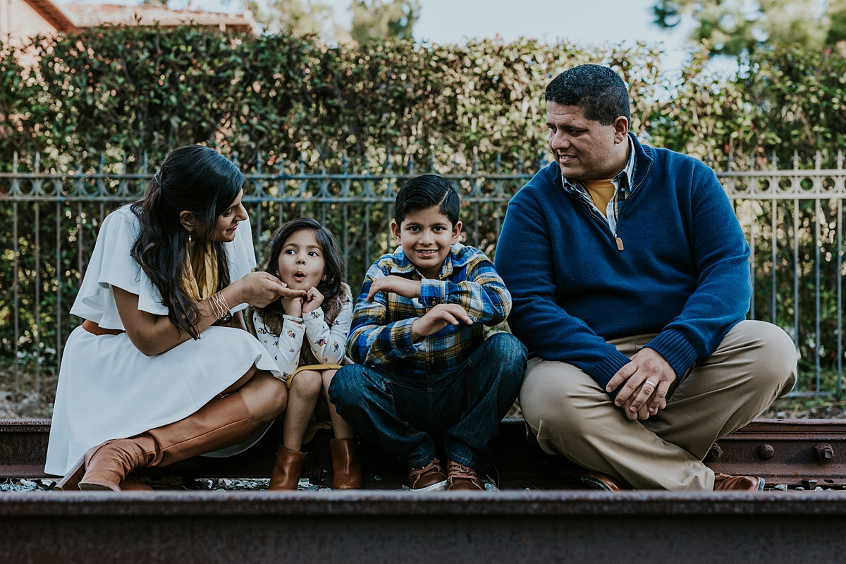 Orange County family photographer. Candid photo of family of four sitting and making faces at abandoned railway tracks during outdoor family photo shoot in orange county
