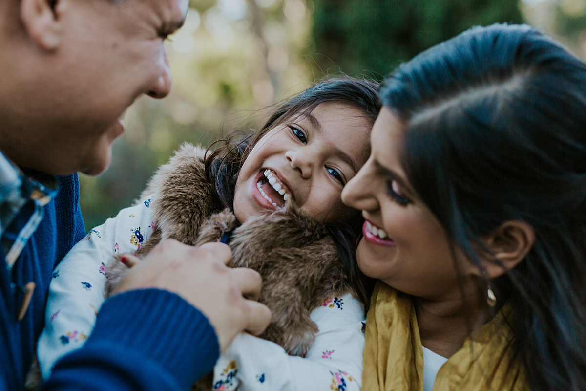 Orange County family photographer. candid photo of dad, mom and sweet young daughter laughing happily during outdoor family photo shoot in orange county