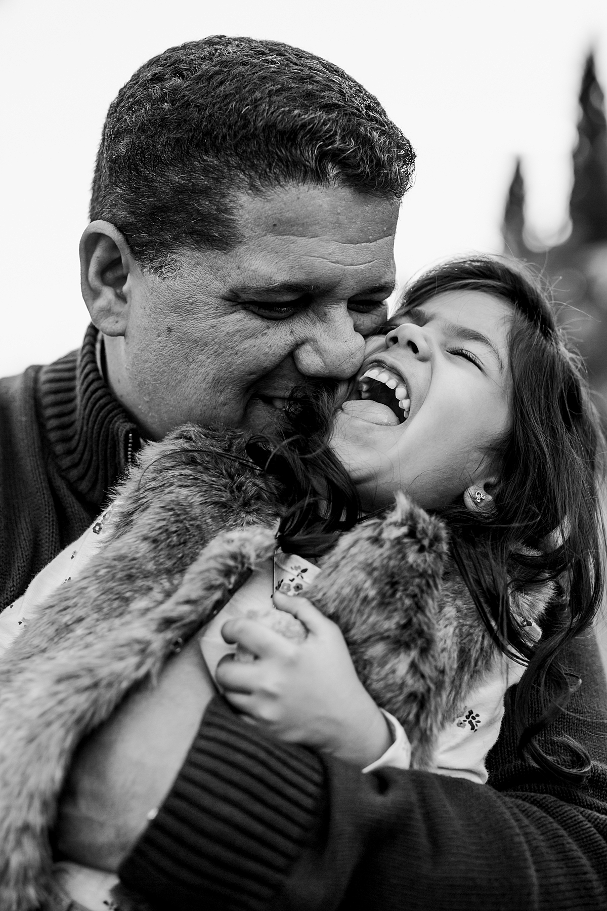 Orange County family photographer. Candid photo of dad tickling daughter and daughter laughing pretty hard during outdoor family photo shoot in orange county