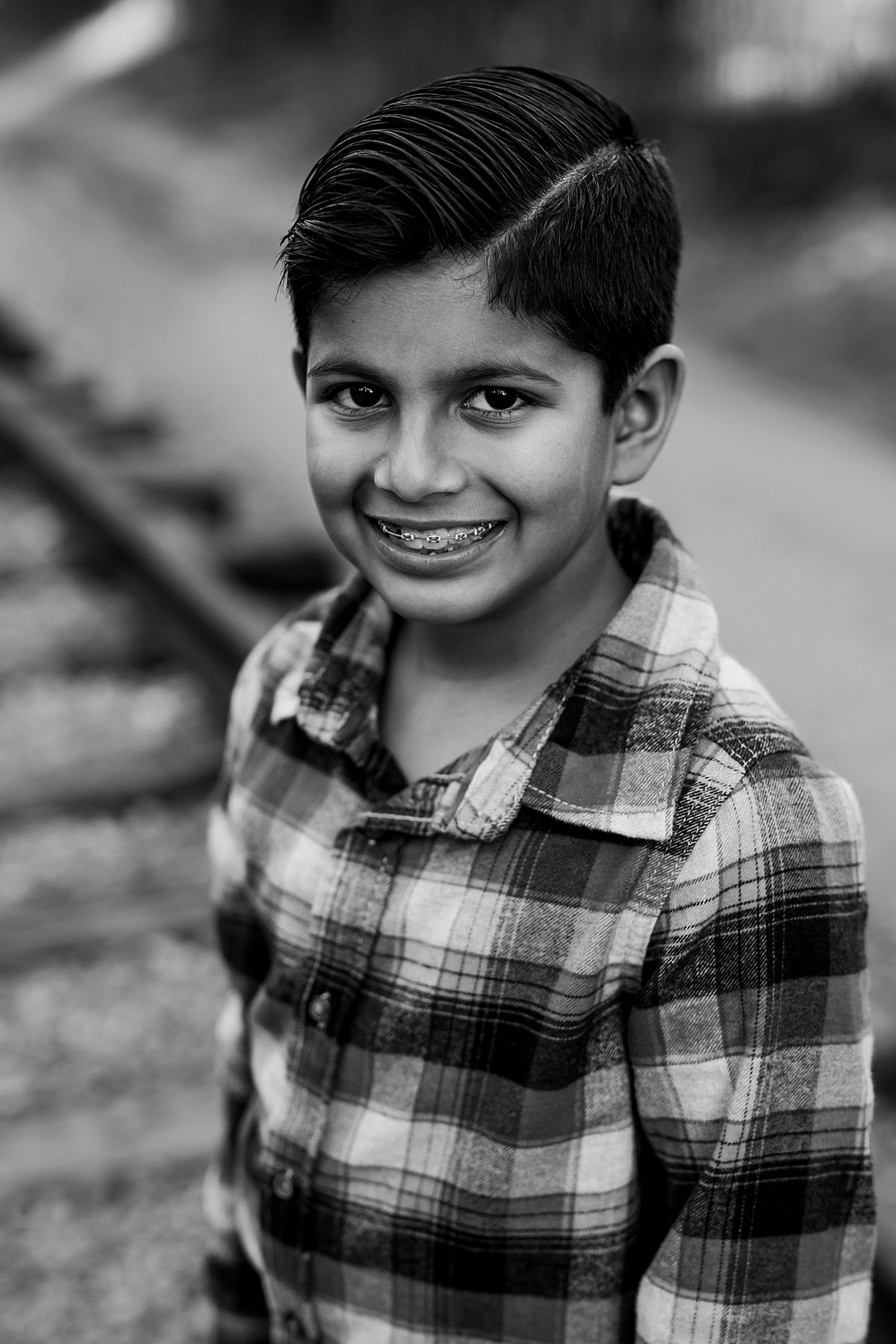 Orange County family photographer. Black and white portrait of sweet boy with adorable braces as he stands on abandoned railway tracks during outdoor family photo shoot in orange county