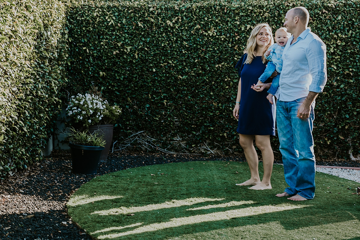 Orange County family photographer. photo of mom, dad and son standing in grass behind their shadows during in home family photo shoot in Huntington Beach