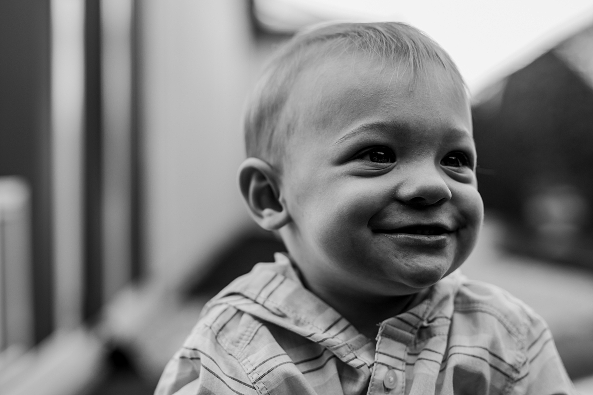 Orange County family photographer. black and white photo of one year old boy in his backyard during in home family photo shoot in Huntington Beach