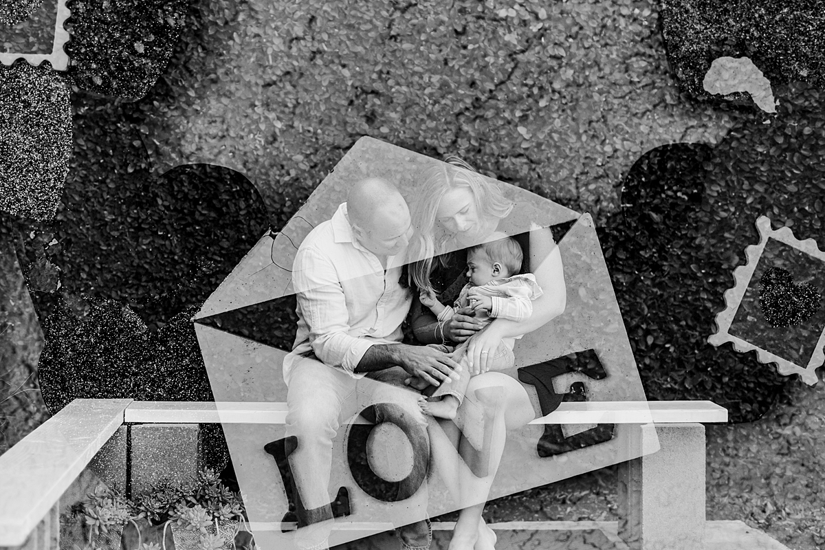 Orange County family photographer. Double exposure photo of mom, dad and son sitting in backyard overlaid with love wall hanging during in home family photo shoot in Huntington Beach