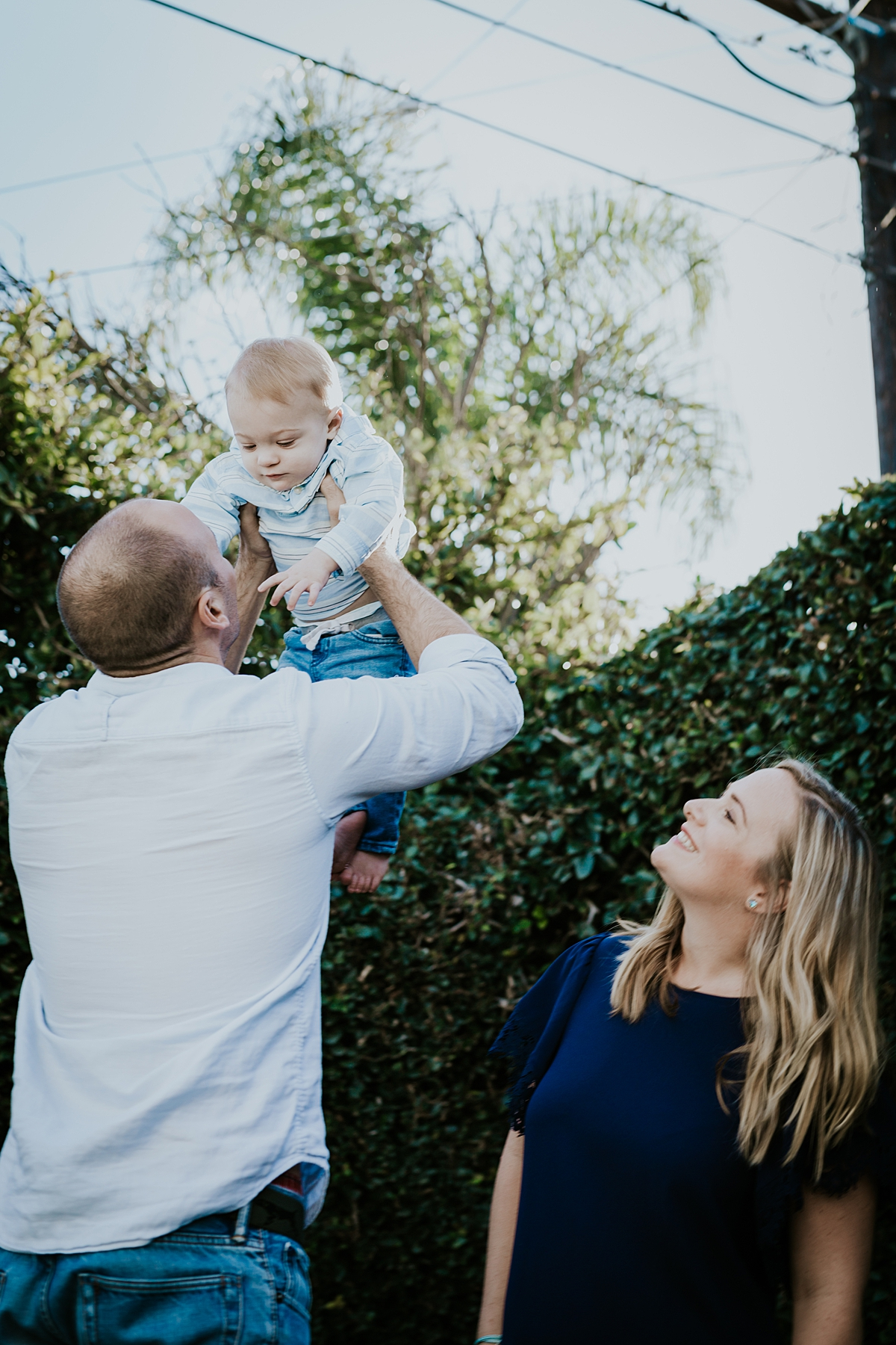 Orange County family photographer. photo of dad throwing son in the air while mom watches during in home family photo shoot in Huntington Beach