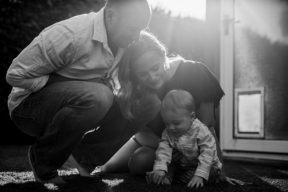 Orange County family photographer. Backlight photo of mom, dad and son sitting in the backyard during in home family photo shoot in Huntington Beach