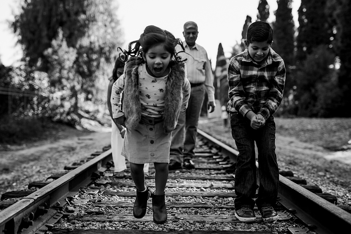 Orange County family photographer. Candid photo of sister and brother as they jump along the abandoned railway tracks during outdoor family photo shoot in orange county