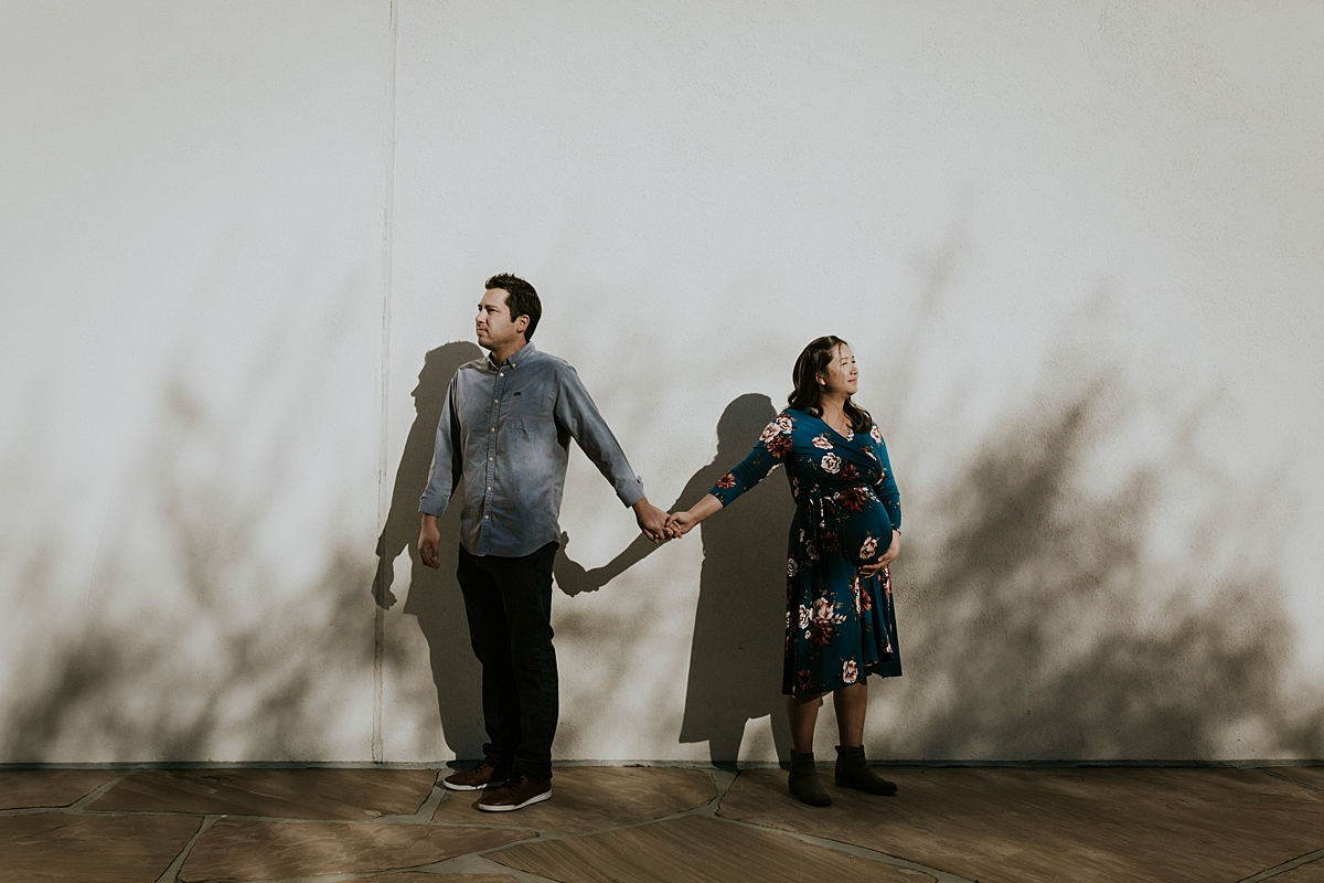 Orange County family photographer. Married couple hold hands n the shadows of garden bushes during maternity photo shoot at Noguchi Garden Costa Mesa