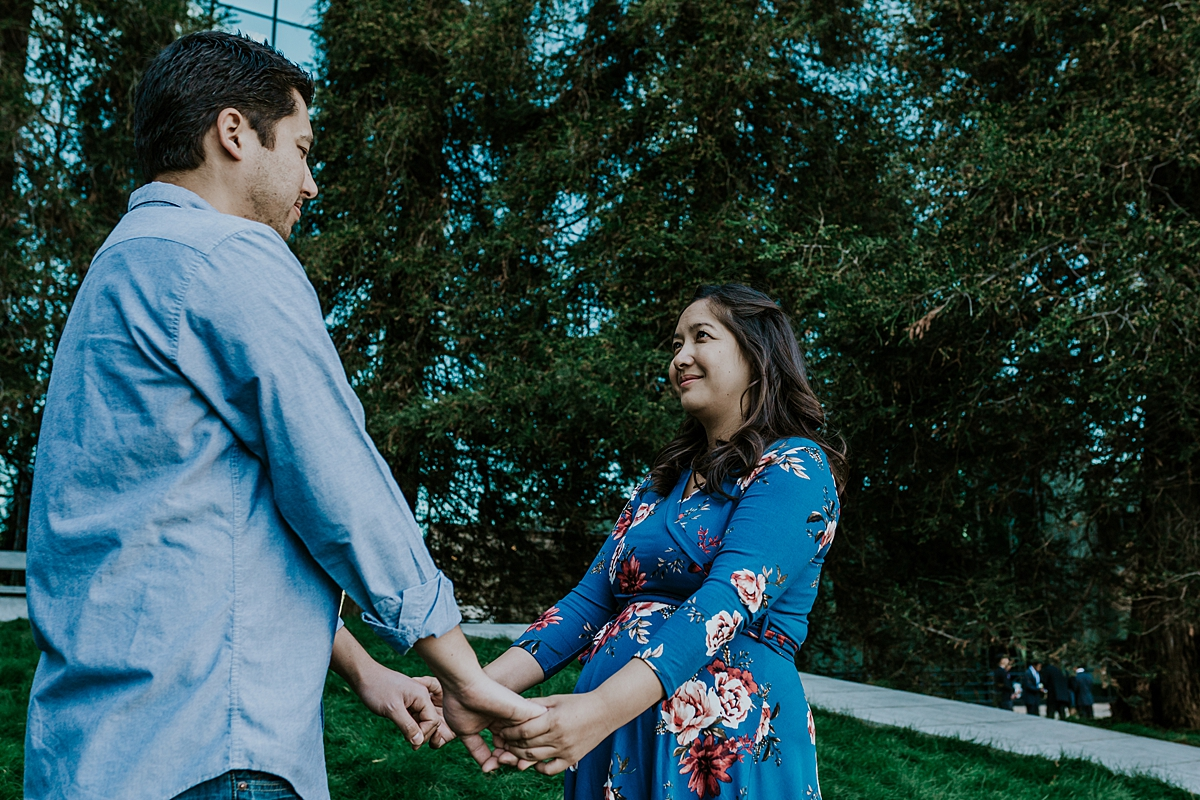 Orange County family photographer. Photo of expecting couple standing among the big of green trees during maternity photo shoot at Noguchi Garden Costa Mesa