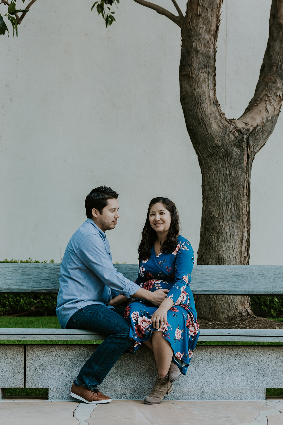 Orange County family photographer. Photo of couple casually sitting on park bench during maternity photo shoot at Noguchi Garden Costa Mesa