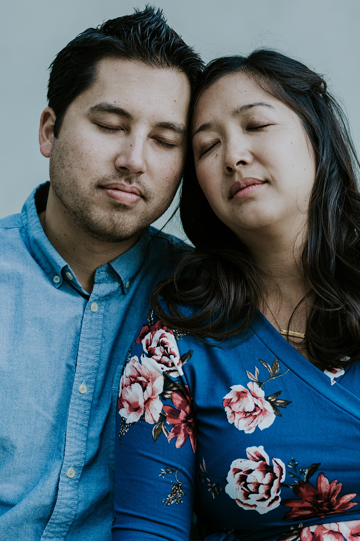 Orange County family photographer. Relaxed portrait photo of couple sitting with their eyes closed during maternity photo shoot at Noguchi Garden Costa Mesa