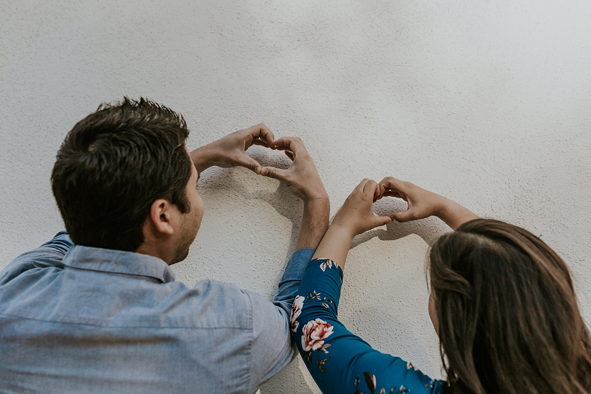 Orange County family photographer. photo of pregnant mother and father to be making love hearts with their hands during maternity photo shoot at Noguchi Garden Costa Mesa