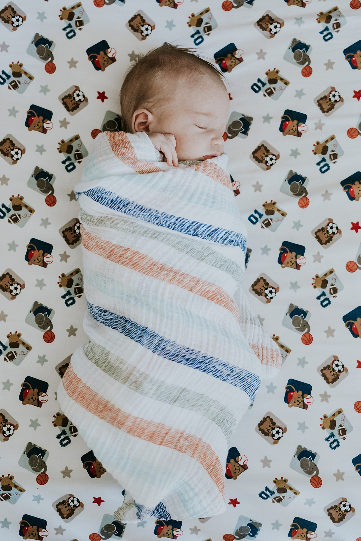Orange County family photographer. Photo of swaddled newborn  baby boy sleeping in his crib during newborn photo shoot in Mission Viejo Orange County