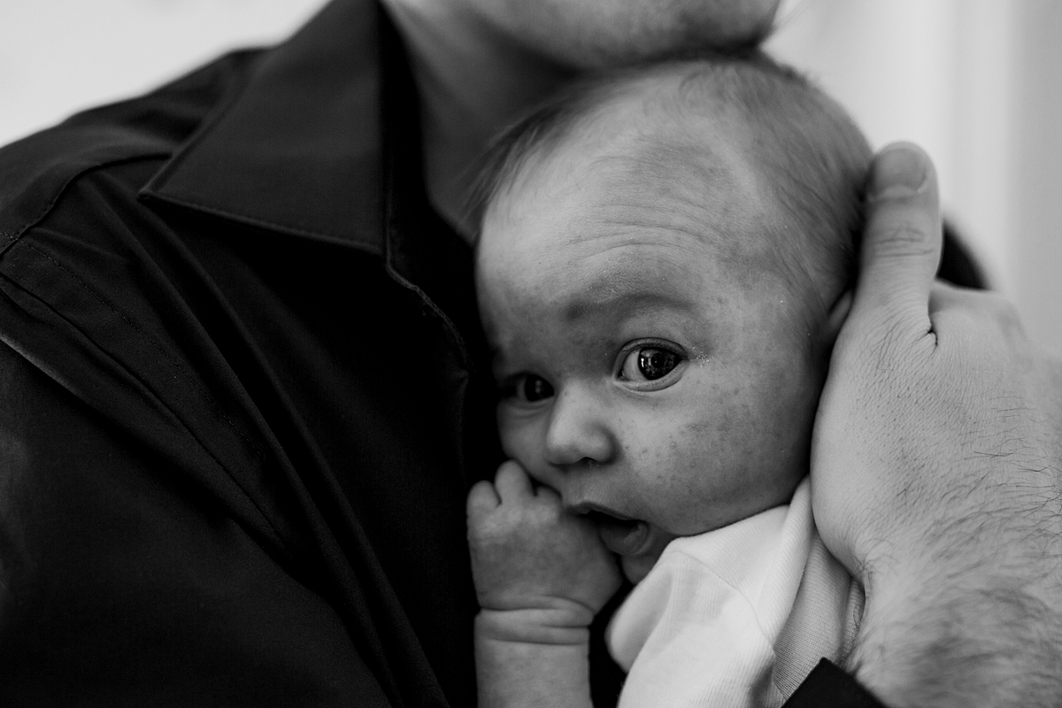 Orange County family photographer. Photo of dad holding his newborn son as he looks straight at the camera while chewing his finger during newborn photo shoot in Mission Viejo Orange County