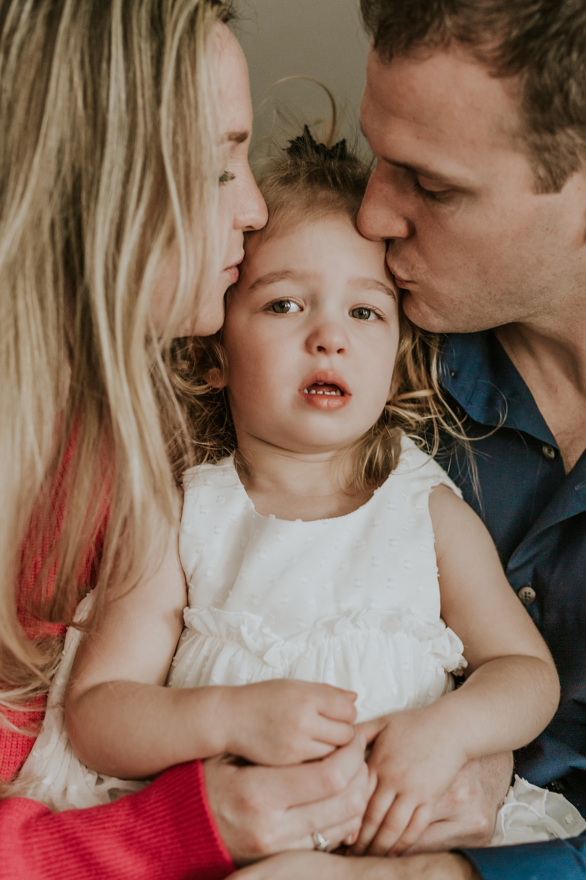 Orange County family photographer. Photo of mom and dad kissing daughter dressed in beautiful white dress during newborn photo shoot in Mission Viejo Orange County