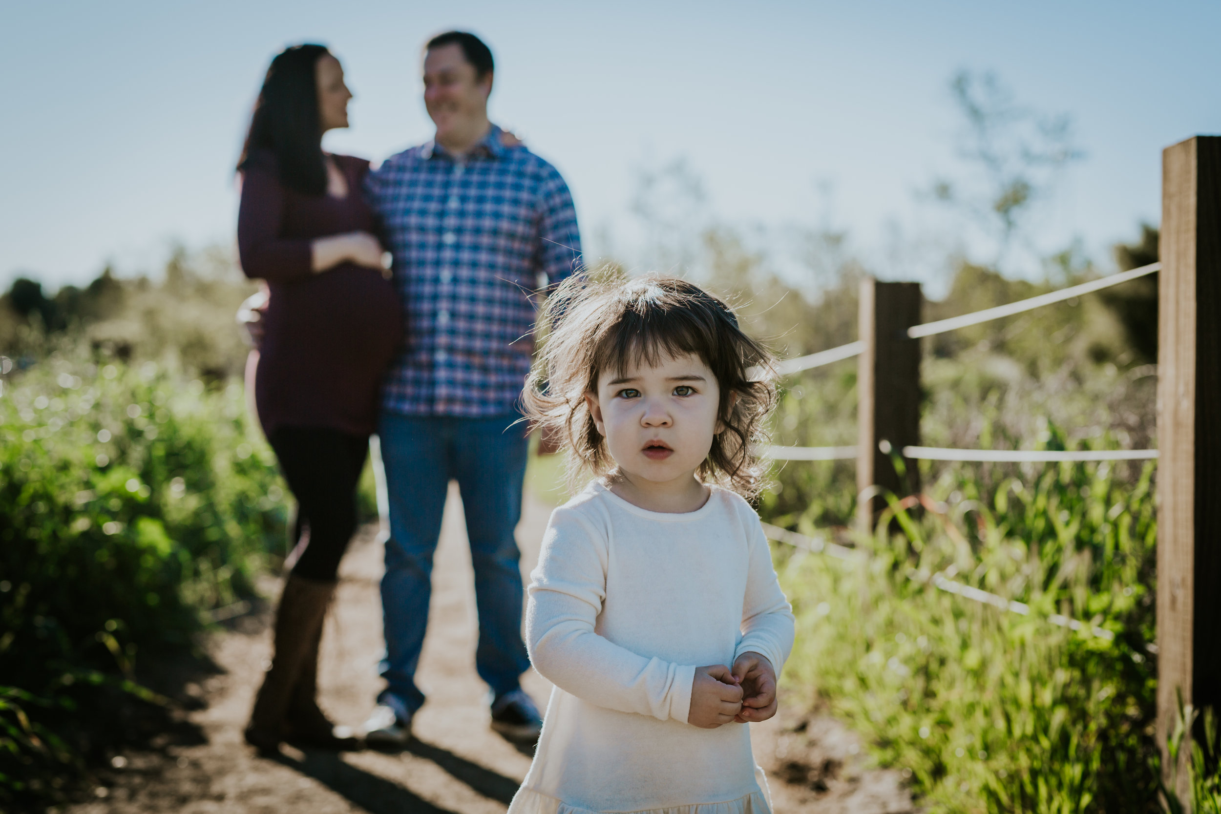 Orange County family photographer. Pregnant mom and dad stand with young toddler daughter during maternity photo shoot among bright green fields at Quail Hill Irvine