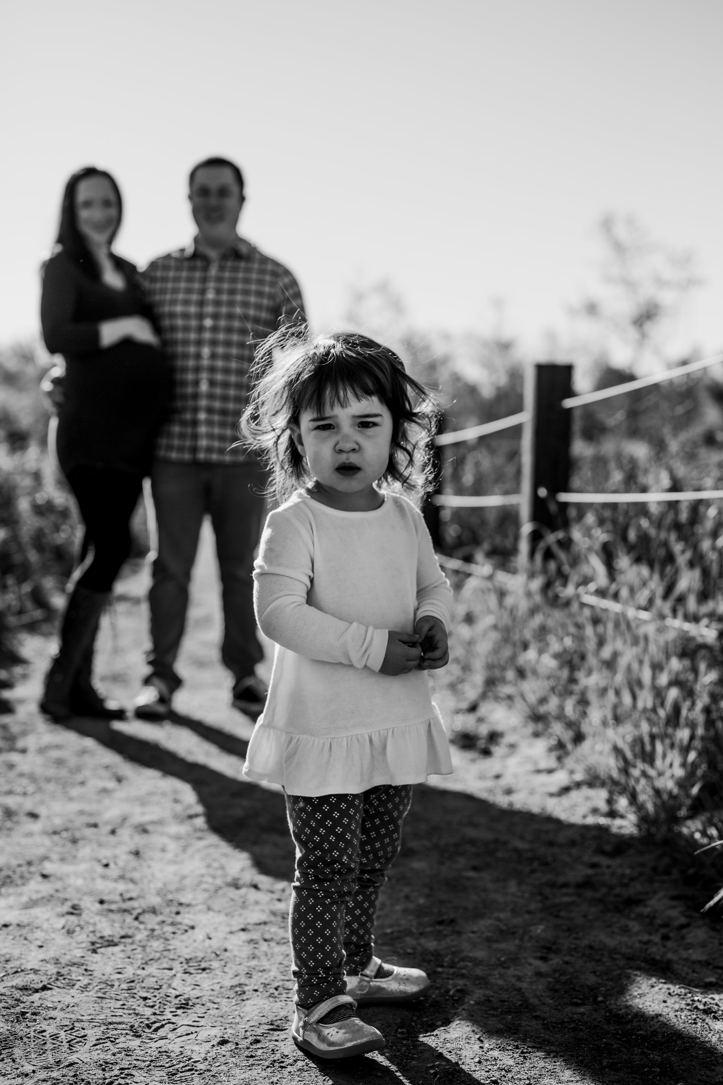 Orange County family photographer. Pregnant mom and dad stand with young toddler daughter during maternity photo shoot in green fields at Quail Hill Irvine