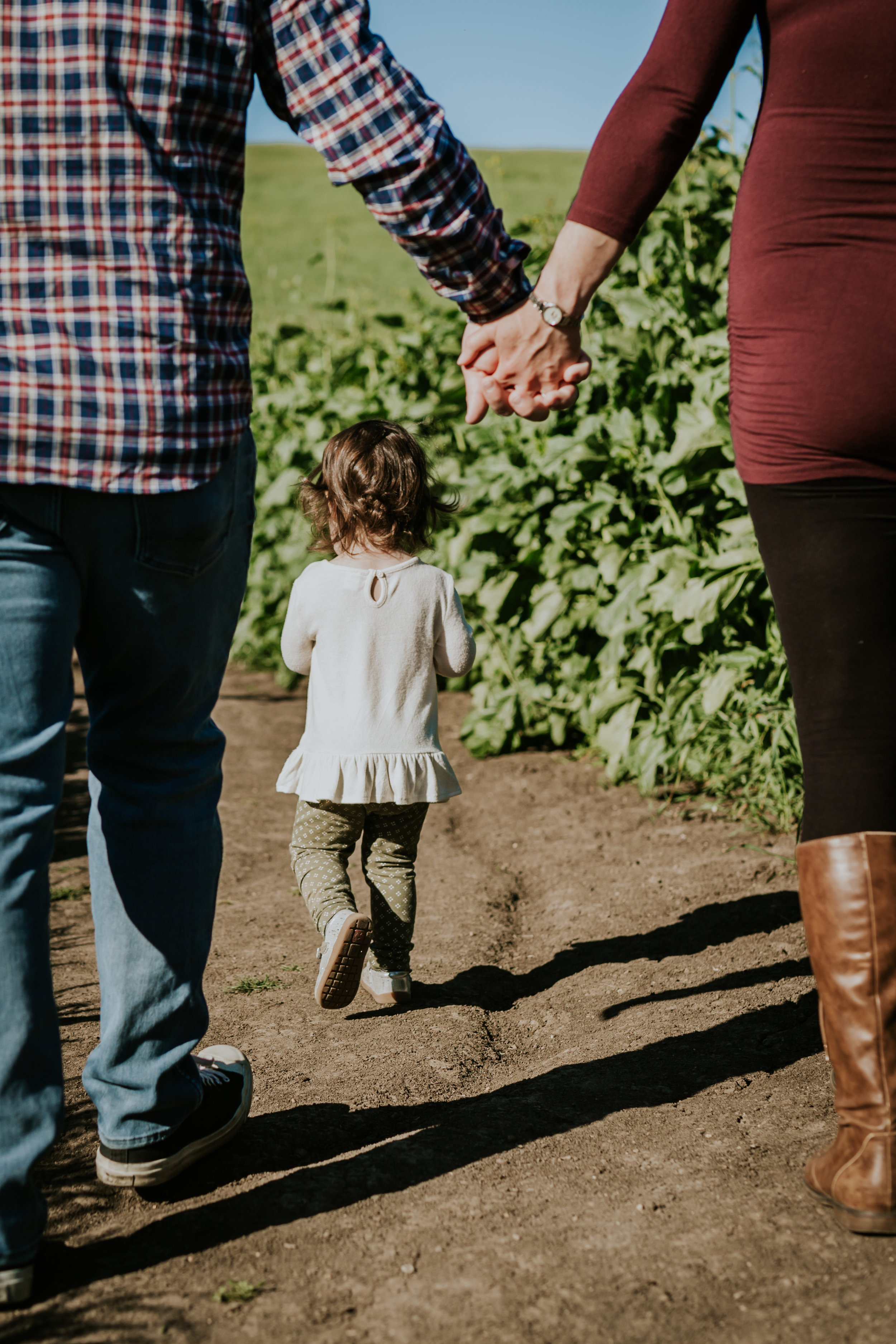 Orange County family photographer. Photo of mom and dad holding hands while young daughter walks in front along walking tracks during maternity photo shoot at Quail Hill Irvine