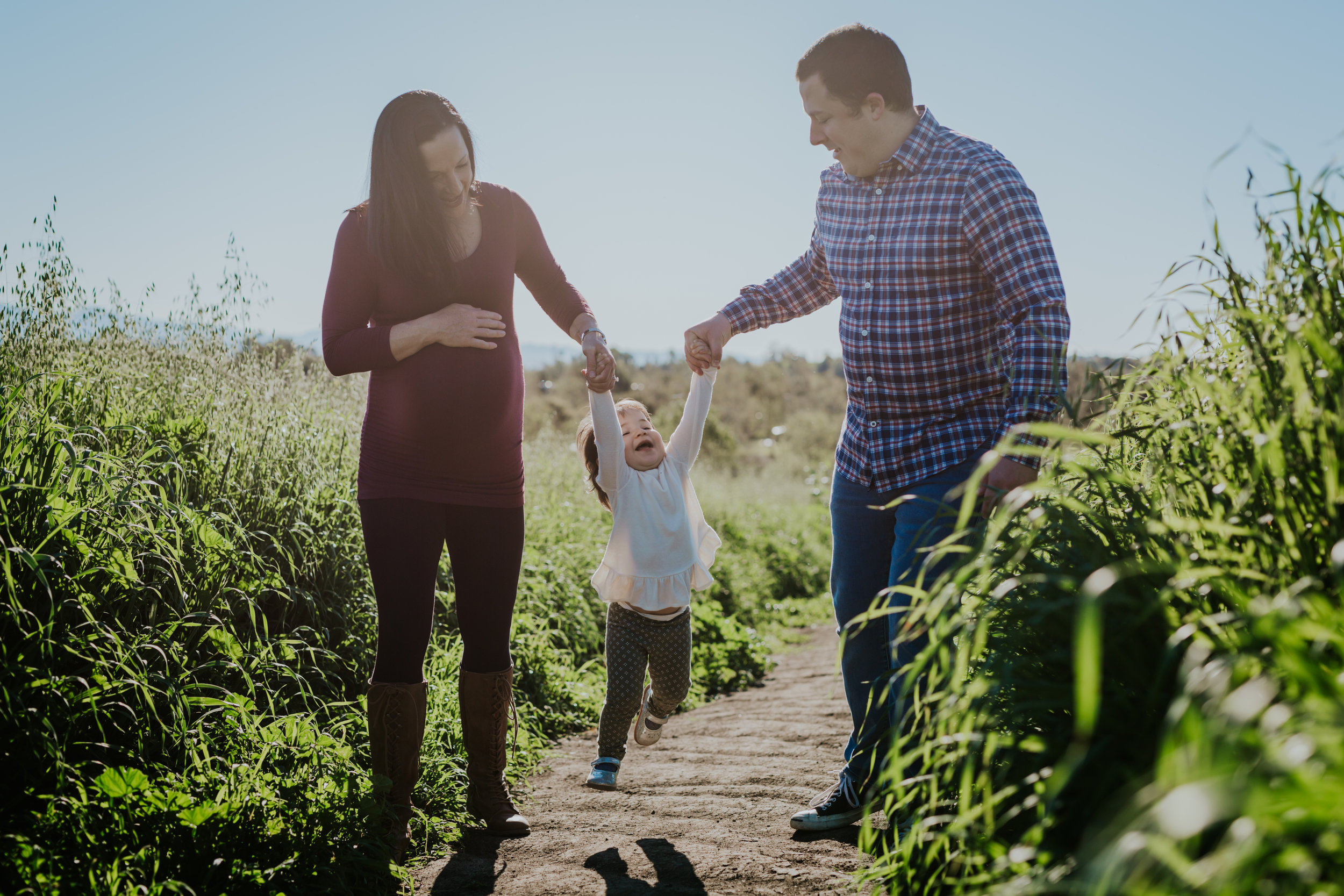Orange County family photographer. Photo of pregnant mom and dad swinging their sweet first born girl in the sunshine among the green fields at Quail Hill Irvine