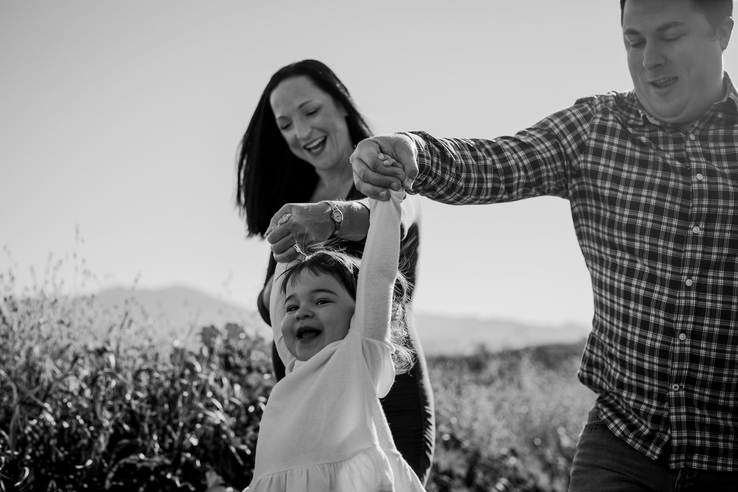 Orange County family photographer. Black and white photo of mom and dad holding hands of their first born as they walk along tracks during maternity photo shoot at Quail Hill Irvine