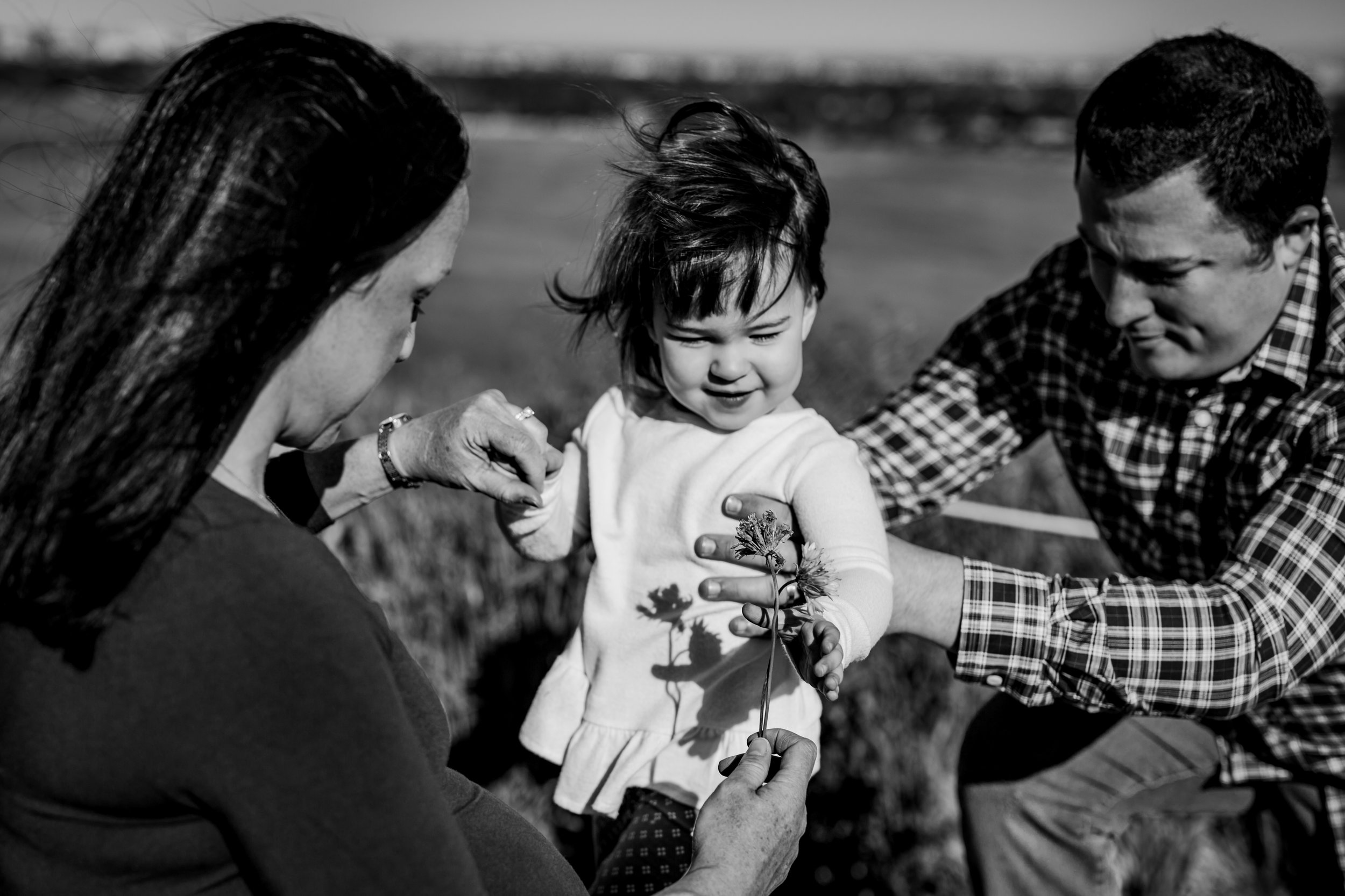 Orange County family photographer. Candid photo of mom and dad holding their daughter in the fields during maternity photo shoot at Quail Hill Trailhead Irvine