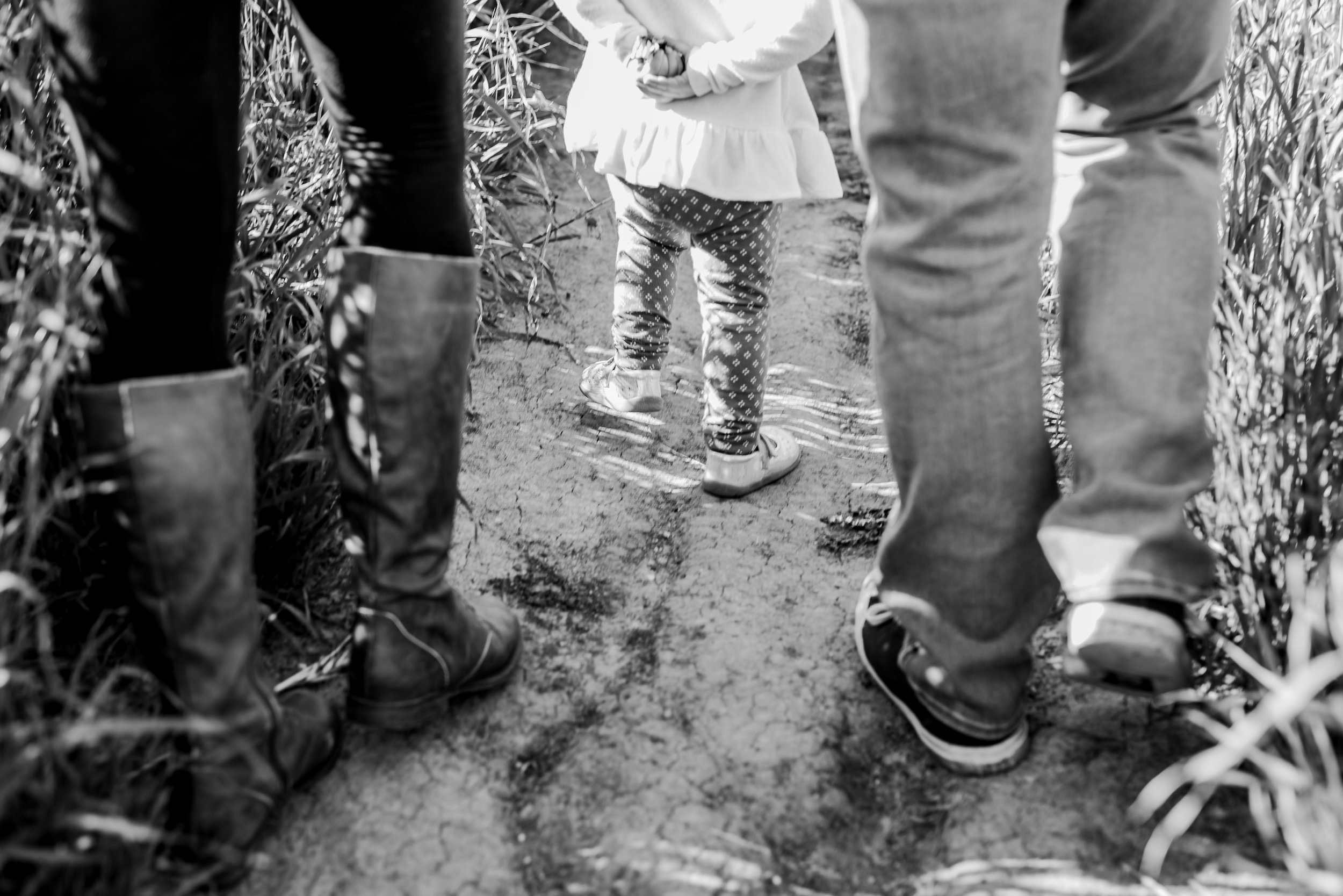Orange County family photographer. Black and white photo of feet of mom, dad and their sweet daughter as they walk through the fields during maternity photo shoot at Quail Hill Trailhead Irvine