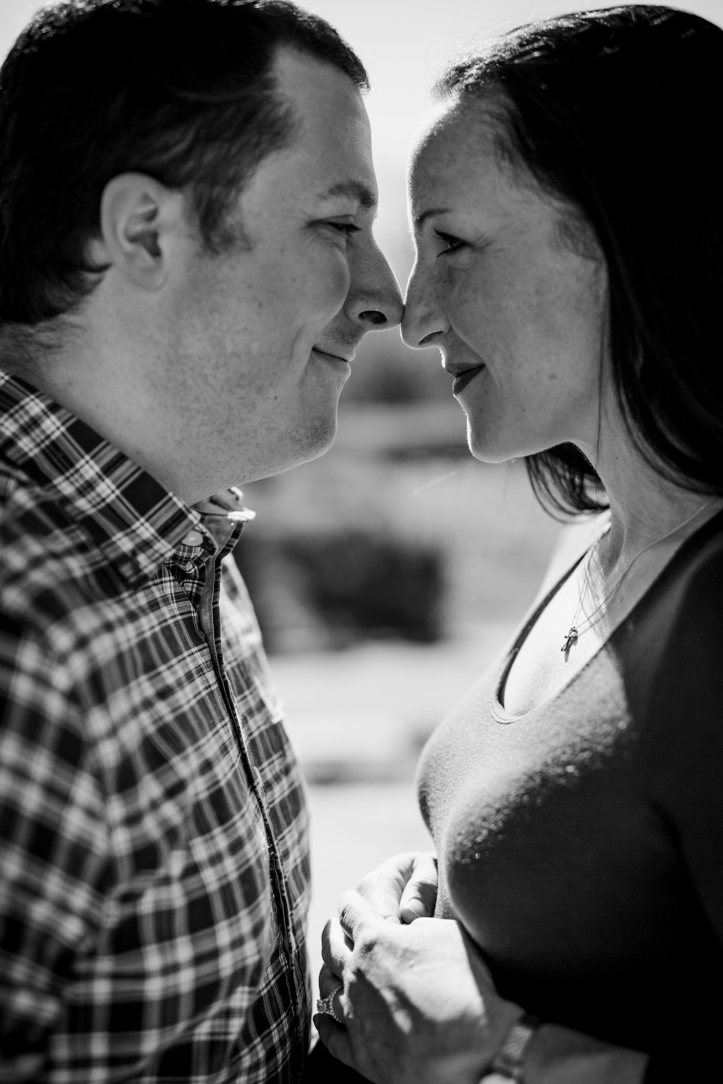 Orange County family photographer. Portrait of mom and dad as their noses touch and they look in each other's eyes during maternity photo shoot at Quail Hill Trailhead Irvine