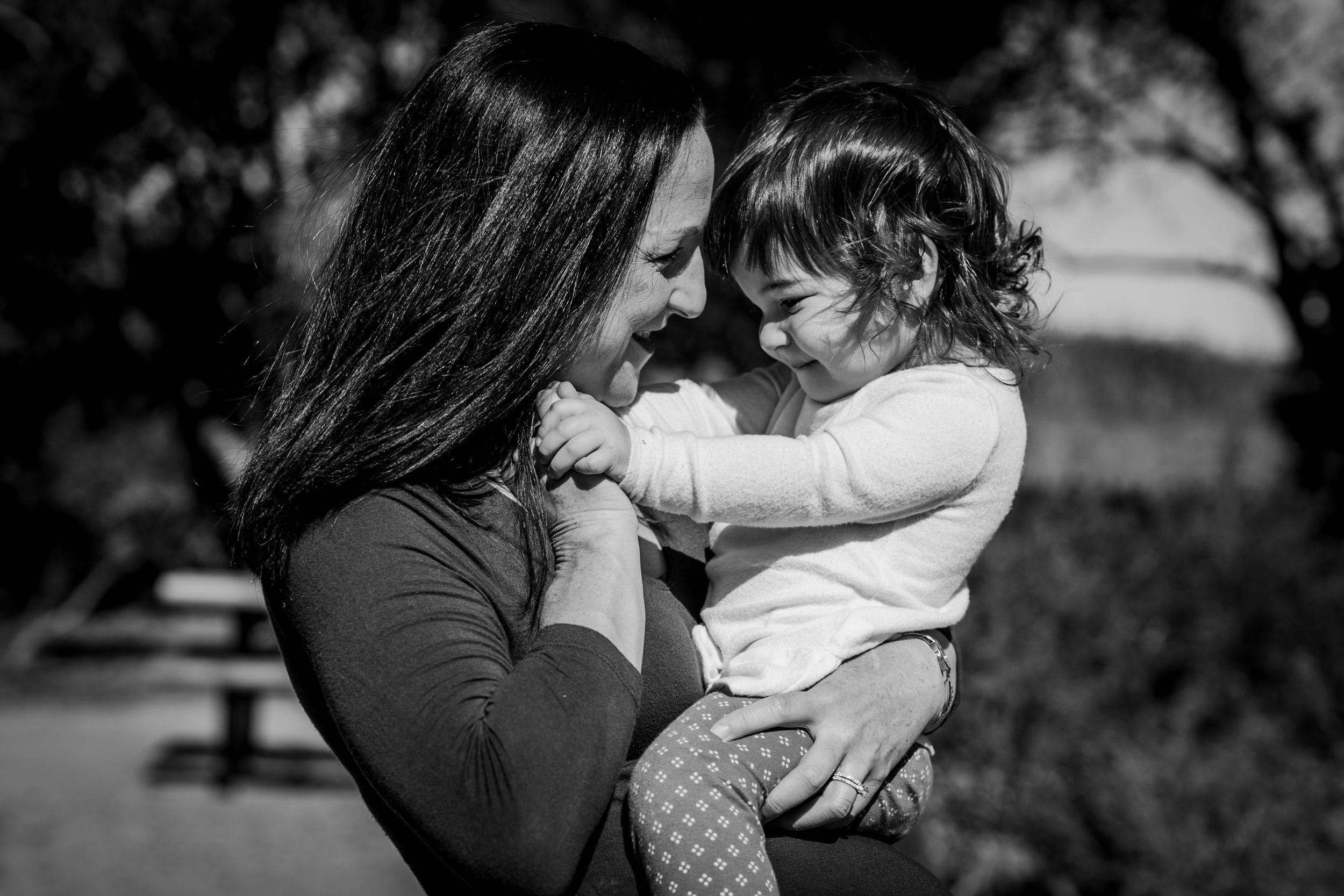 Orange County family photographer. Portrait of pregnant mom as she holds and plays with her sweet daughter during maternity photo shoot at Quail Hill Trailhead Irvine