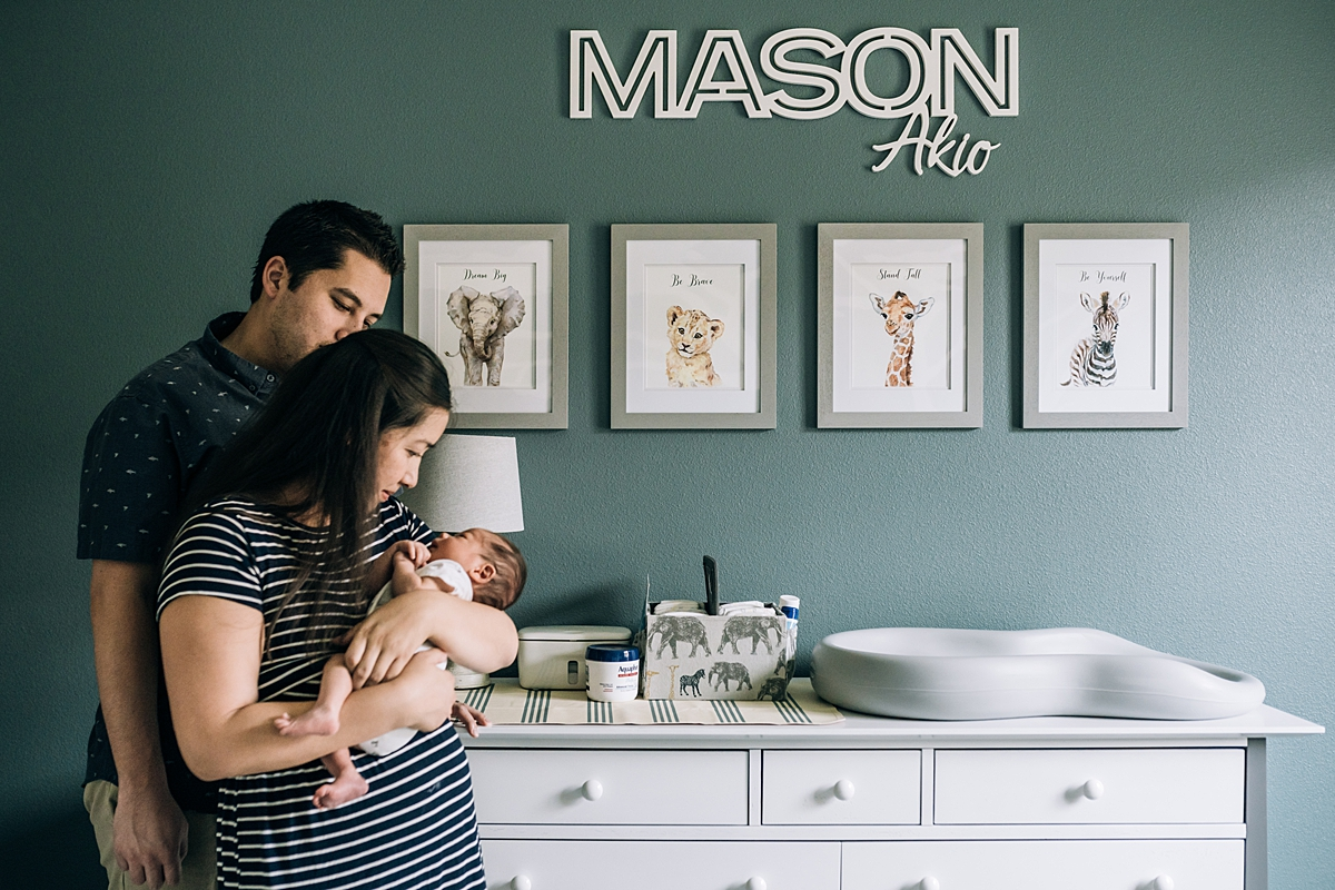 Orange County family photographer. Photo of mom and dad looking at their newborn son in the nursery room with cute animal pictures during newborn photo shoot in Lake Forrest Orange County
