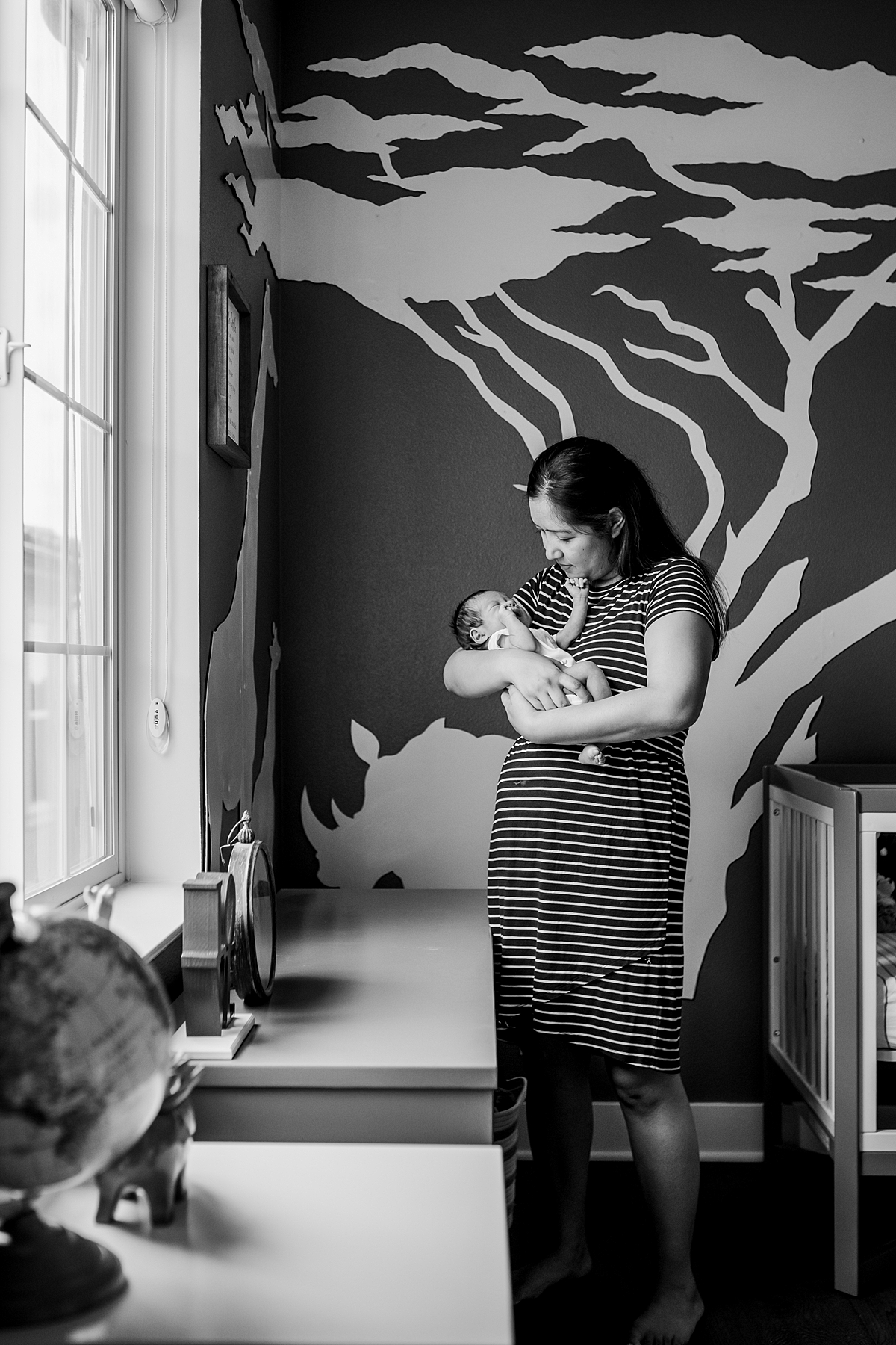 Orange County family photographer. Black and white photo of mom shooshing her sweet newborn son in the nursery during newborn photo shoot in Lake Forrest Orange County