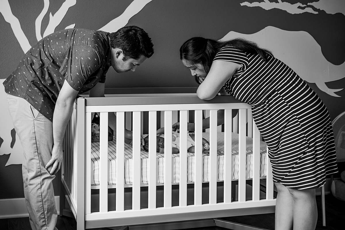 Orange County family photographer. photo of mom and dad interacting with newborn son as he lays in his crib during newborn photo shoot in Lake Forrest Orange County