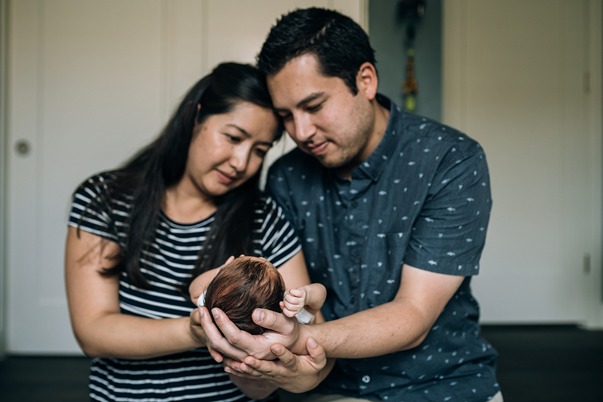 Orange County family photographer. photo of mom and dad holding newborn boy in their arms during newborn photo shoot in Lake Forrest Orange County