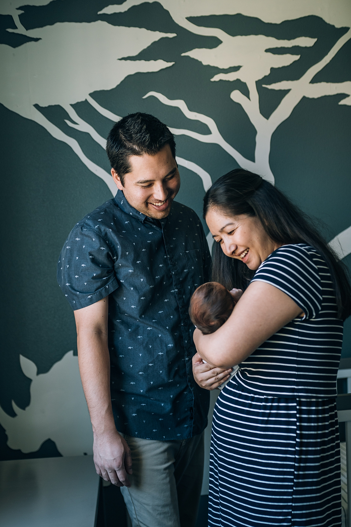 Orange County family photographer. photo of mom and dad standing in nursery talking to their newborn babe during newborn photo shoot in Lake Forrest Orange County