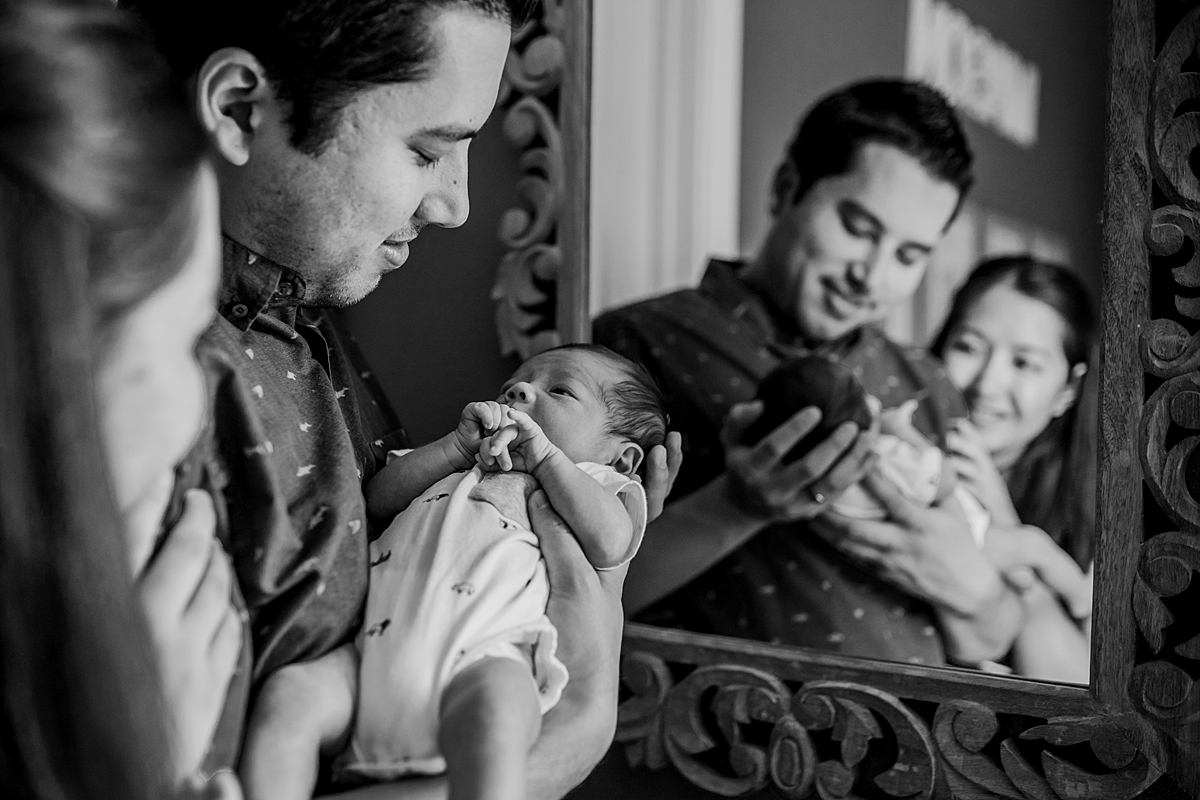 Orange County family photographer. Photo of mom, dad and newborn son looking into the mirror in the baby's nursery during newborn photo shoot in Lake Forrest Orange County