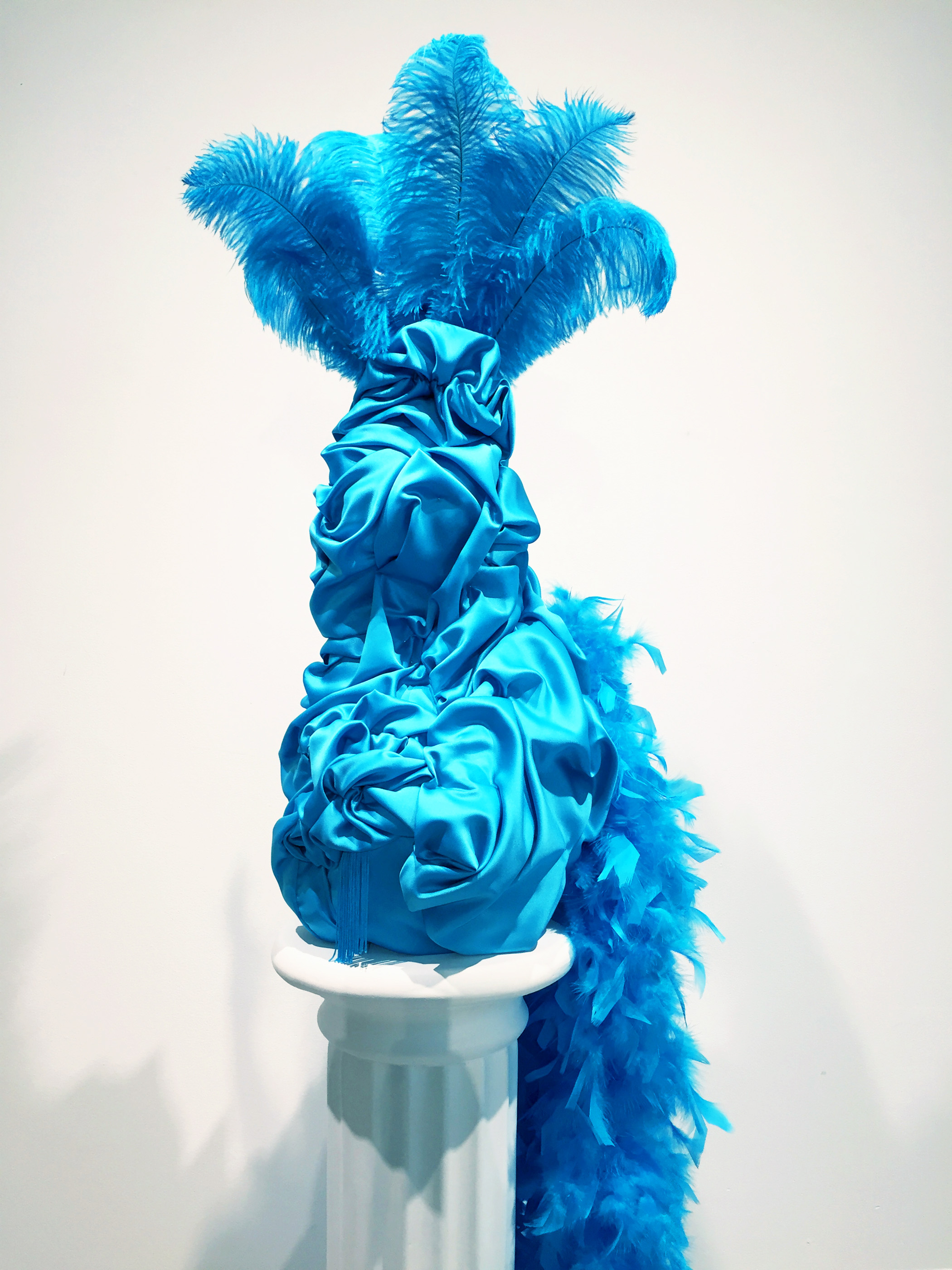 Esma  , 2019   Polystyrene foam, fabrics, feathers, glass beads, sequins and dressmaker pins  31 x 8 x 8 inches