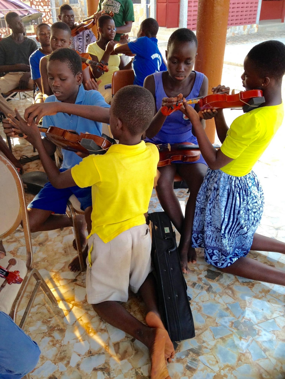 Nunya students helping each other adjust left hand position on the violin