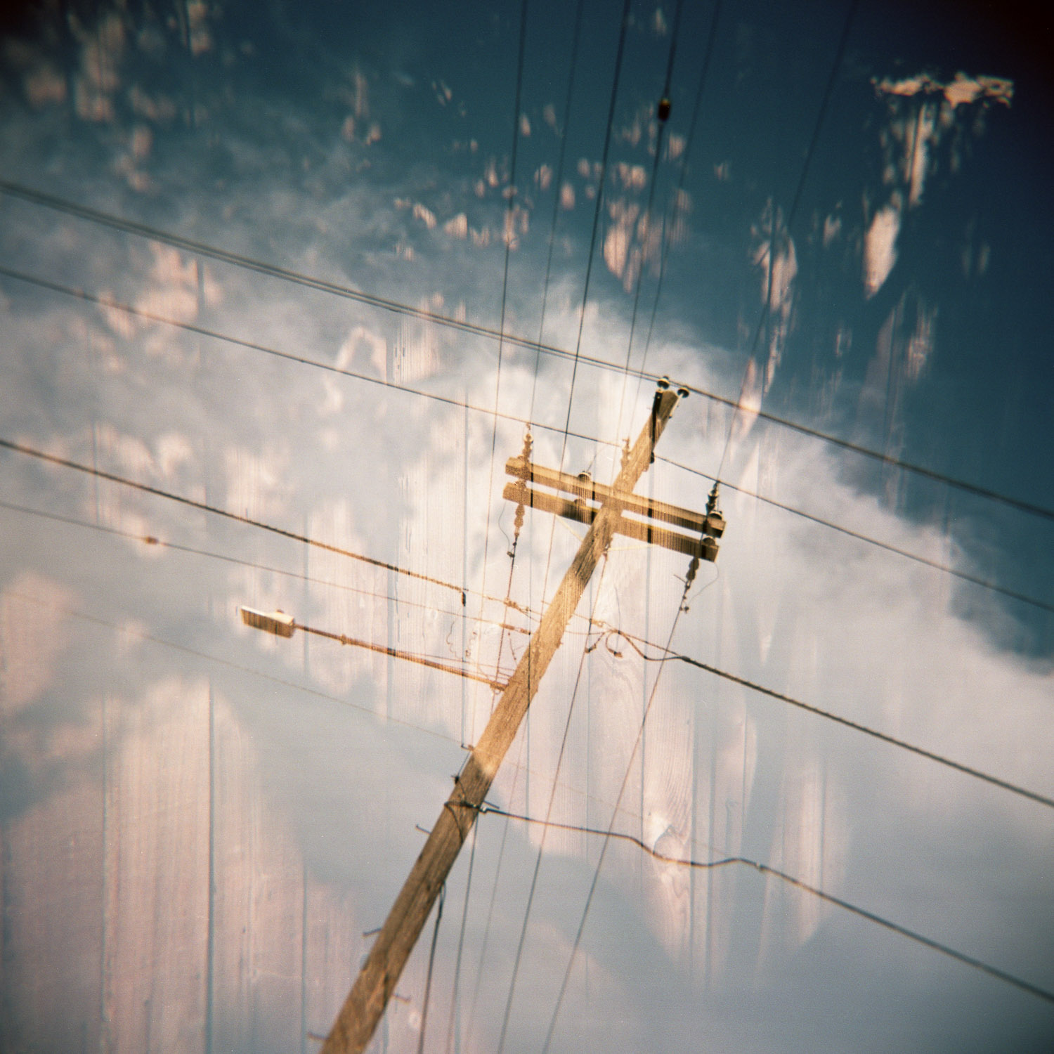 Double exposure Holga photo of power lines and a fence